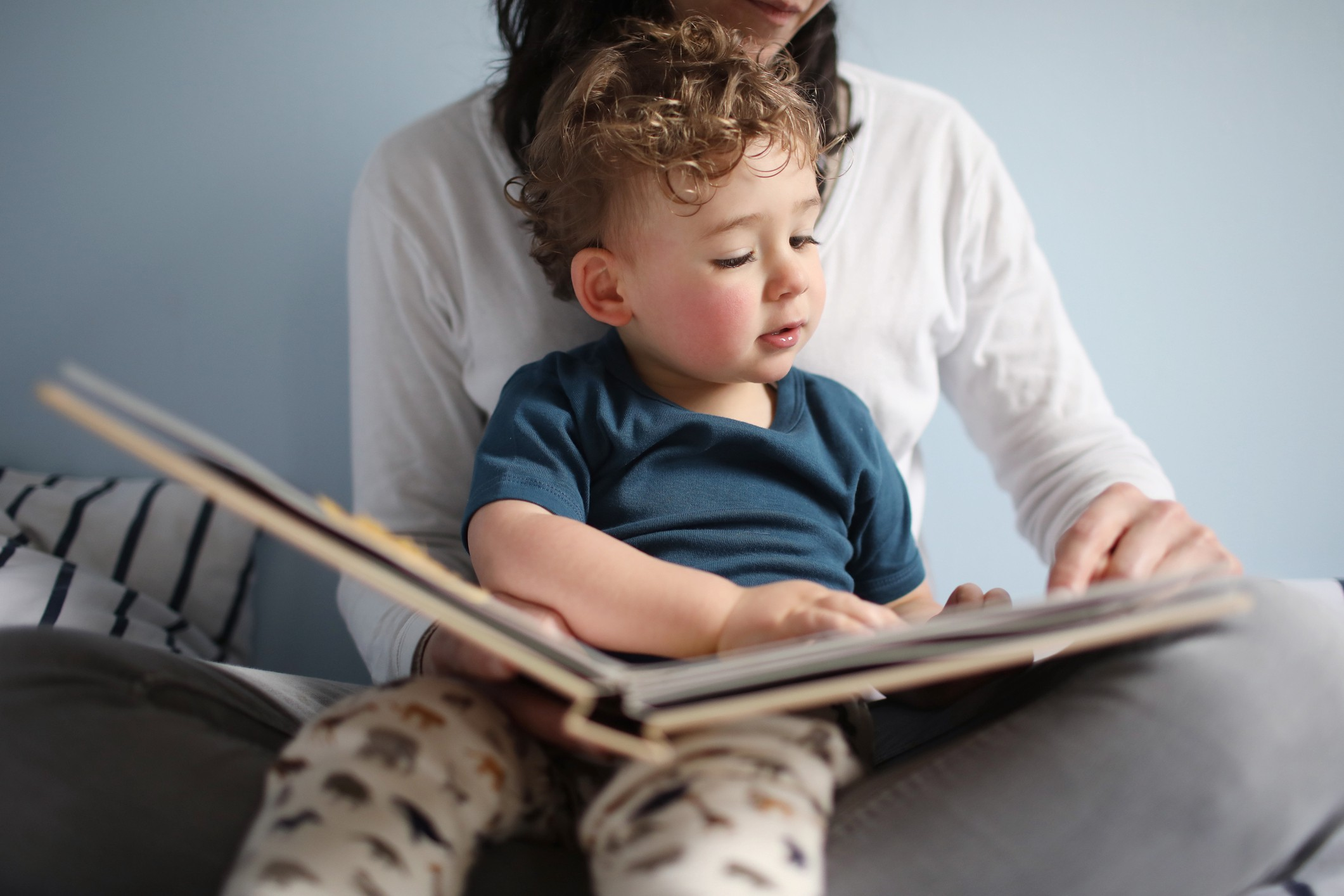 A photo of a mom reading a book to her child sitting in her lap.