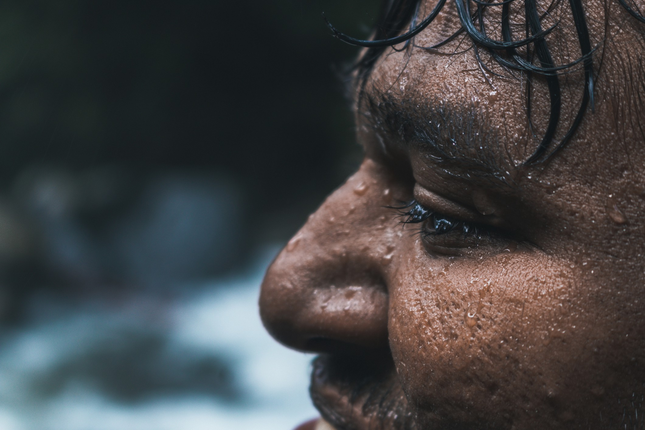 A closeup of a man's face that is wet with rain.