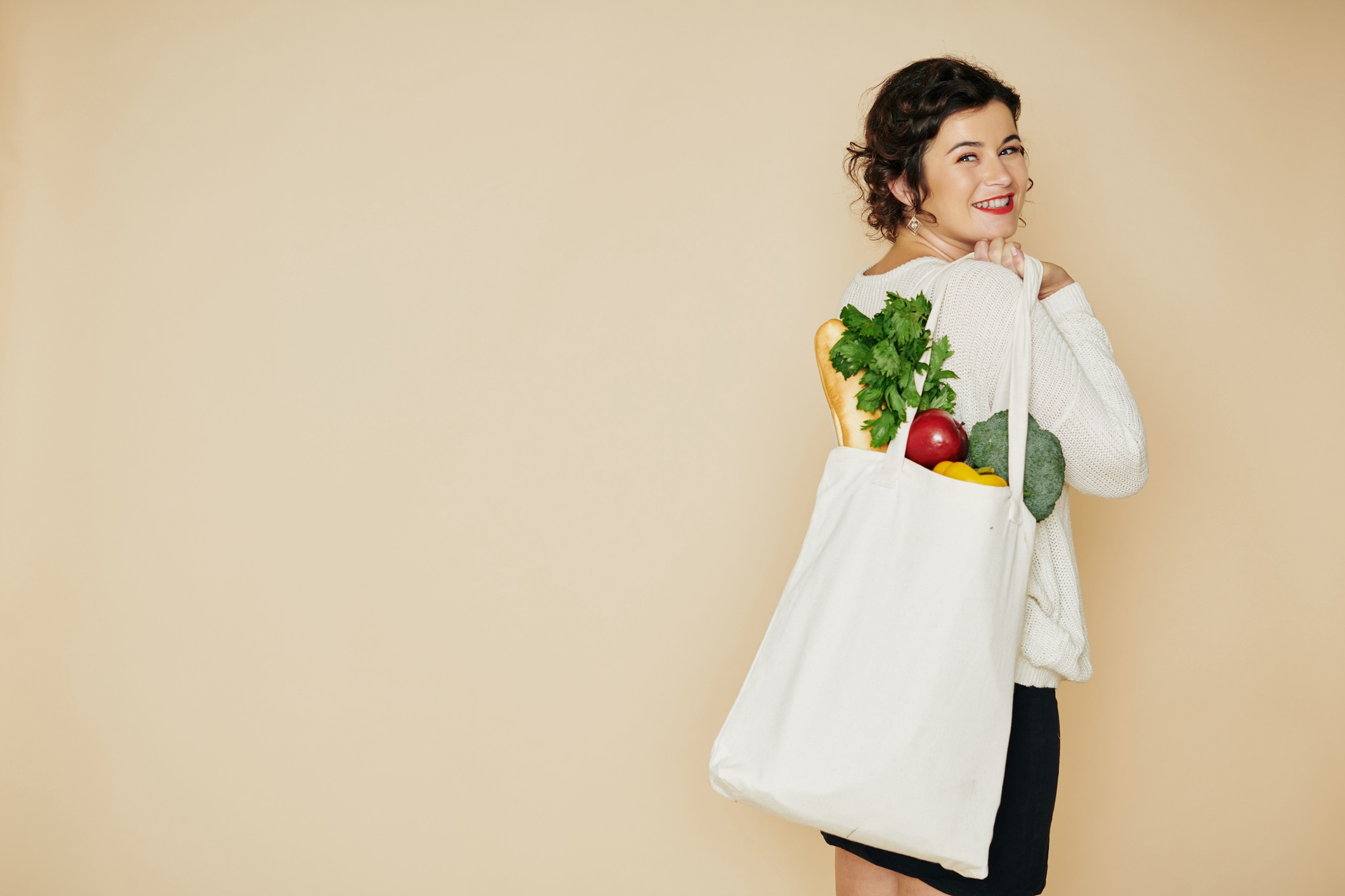 A woman with a shopping bag filled with healthy food slung over her shoulder.