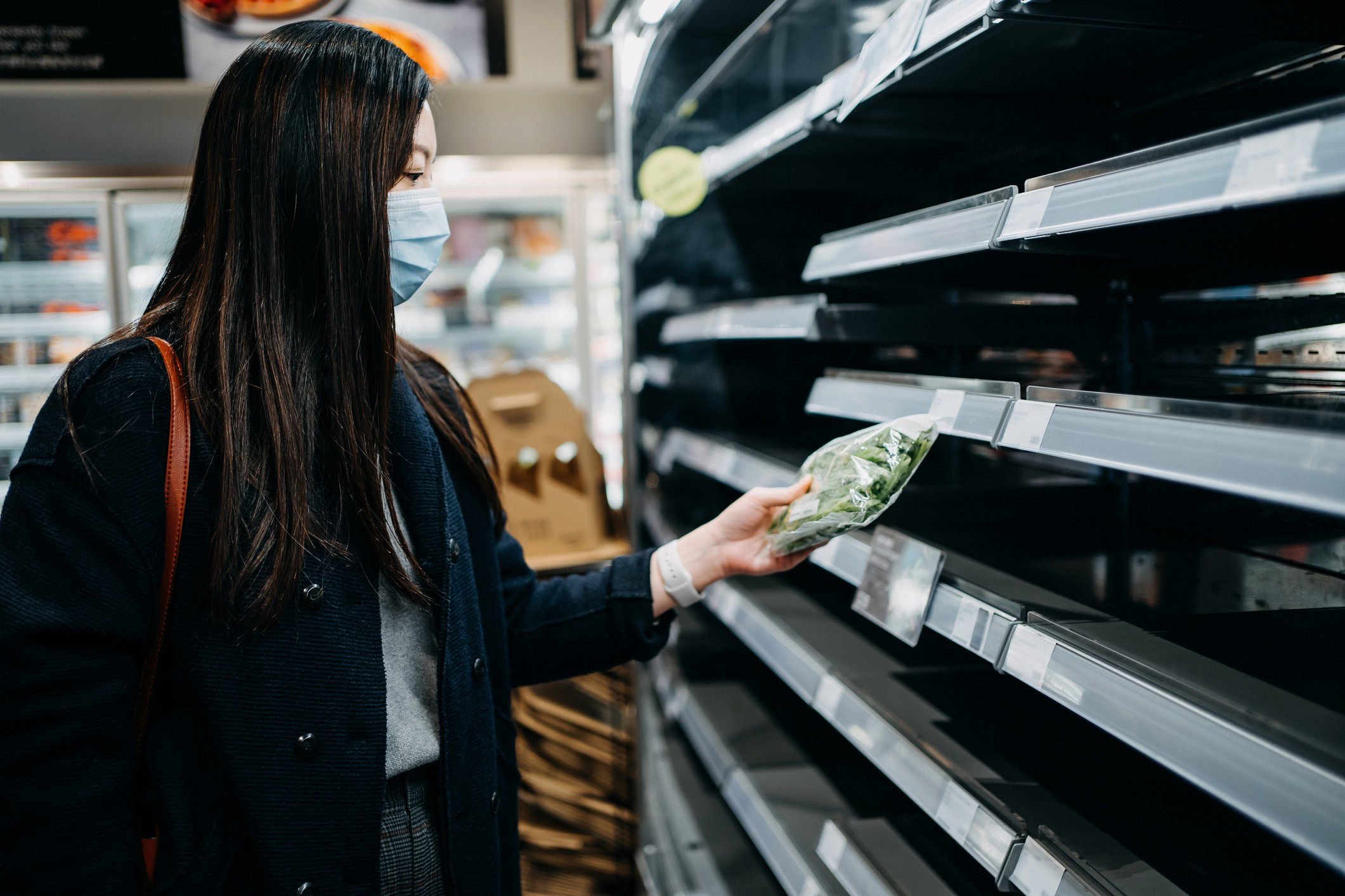 A woman with a mask picks up a packaged meal off of an empty aisle in the supermarket.