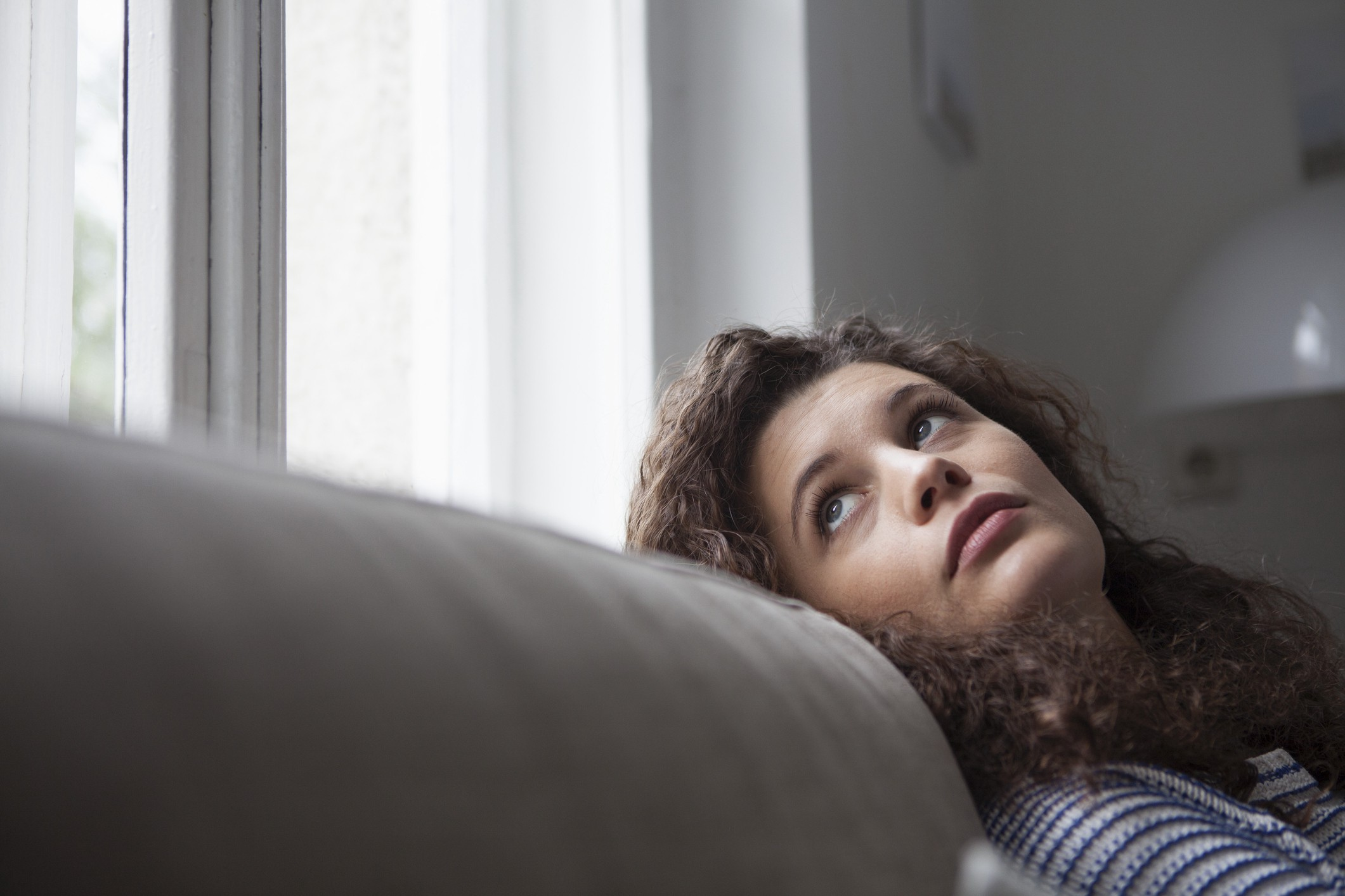 A photo of an annoyed woman looking out the window.