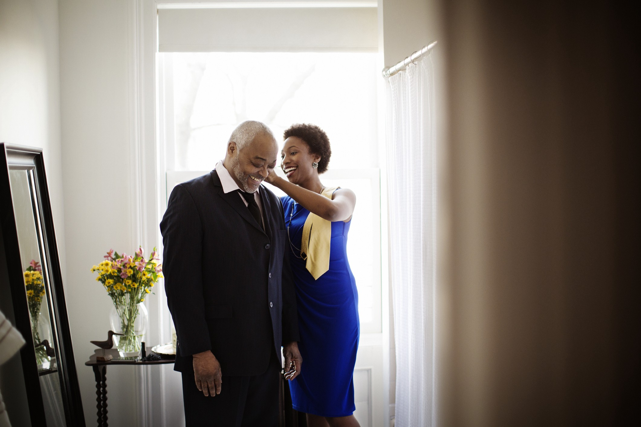 A Black woman assists her elder father with his collar as they prepare for a party.