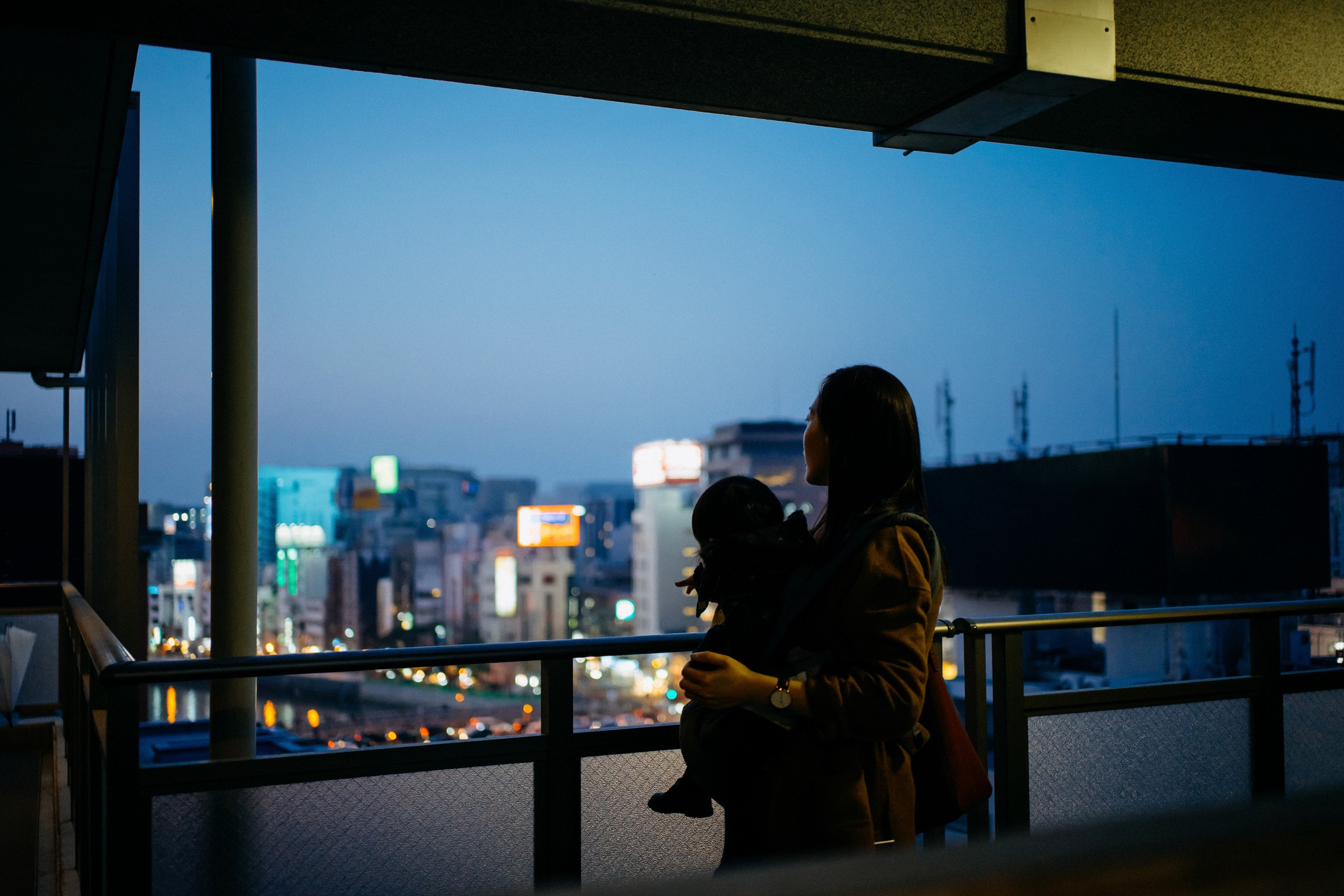Mother with child looking out window at twilight.