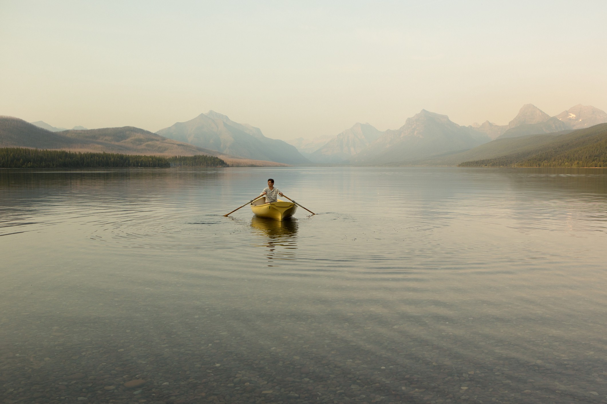 A man rowing a boat in Glacier National Park. Mood is a bit mysterious and muted.