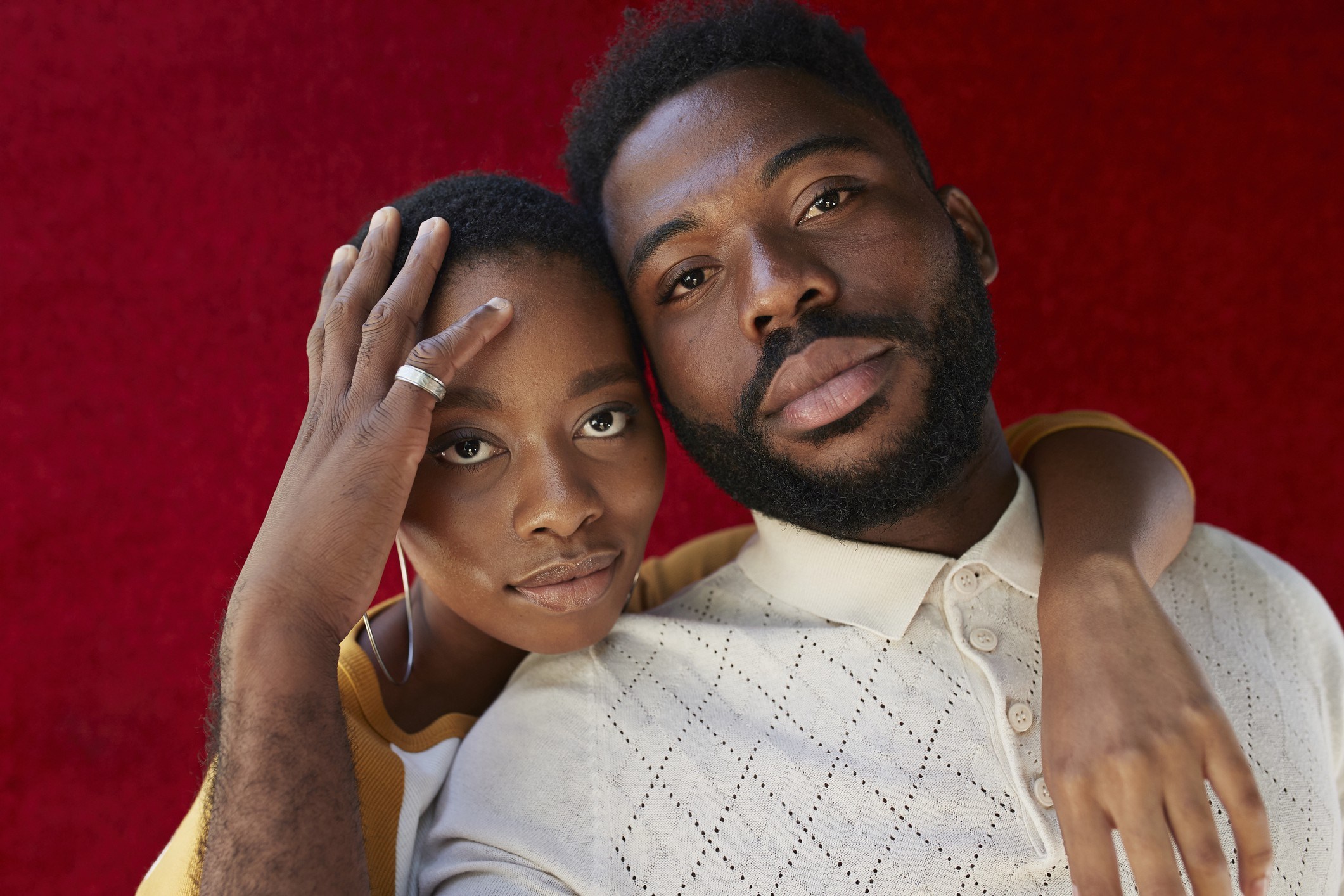 Black man and woman posing together in front of a maroon background.