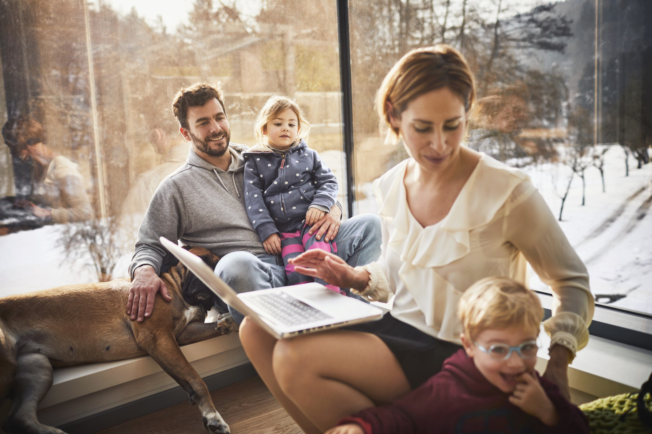 A photo of a family of four (mom, dad, two kids) sitting at home. Mom is on her computer and attending to a child.