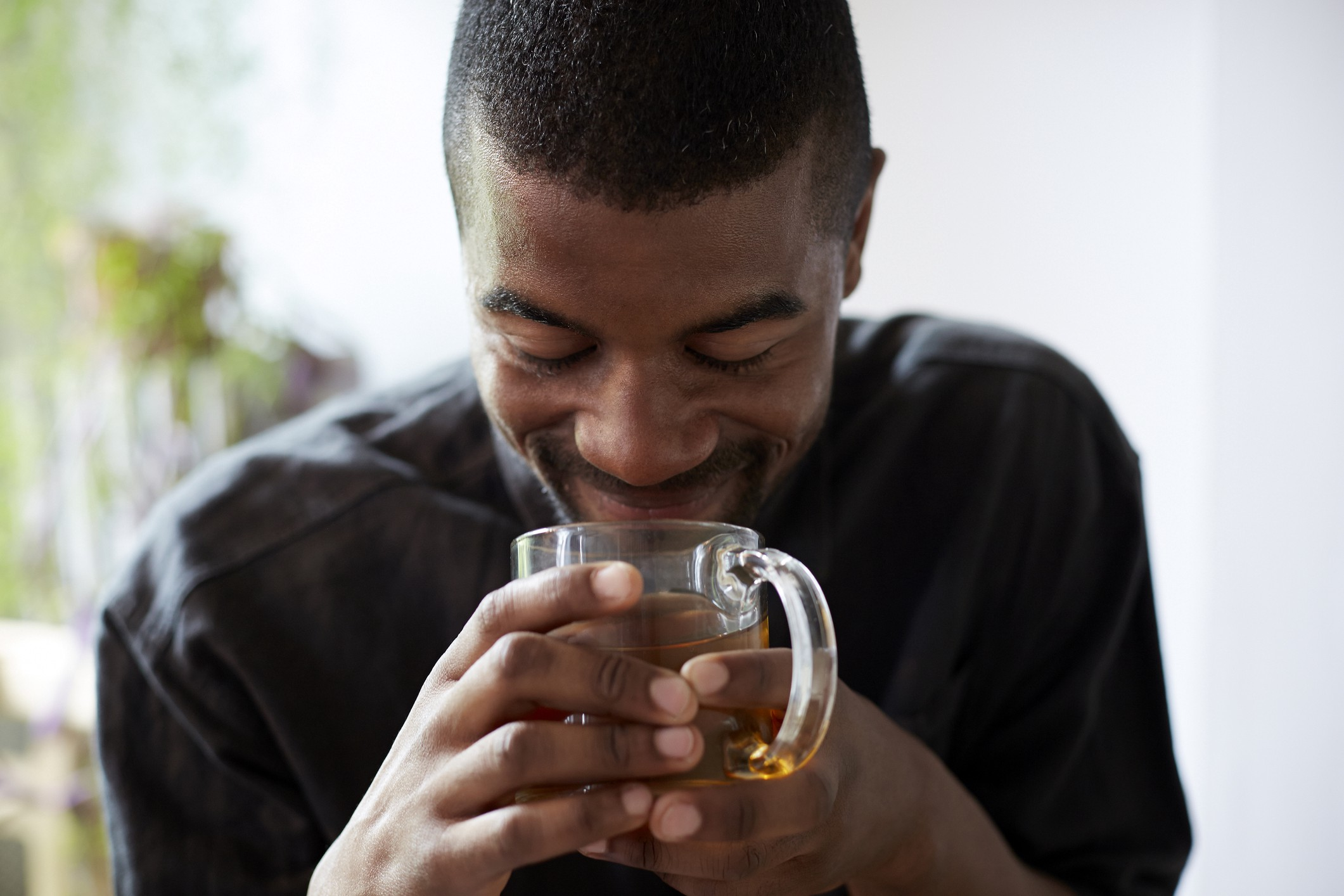 Black man smiling over a cup of tea.
