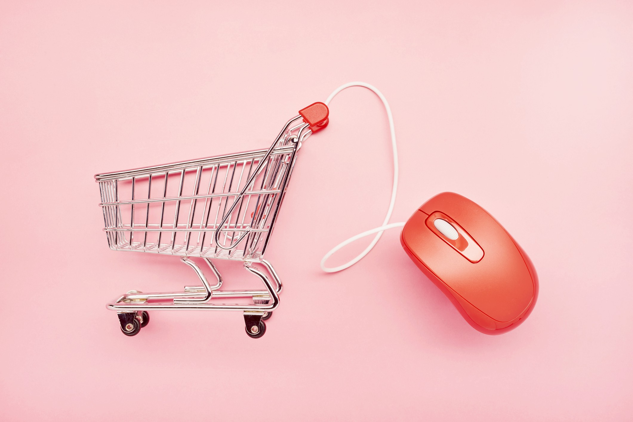 A small shopping cart and red computer mouse on pink background, symbolizing online shopping.