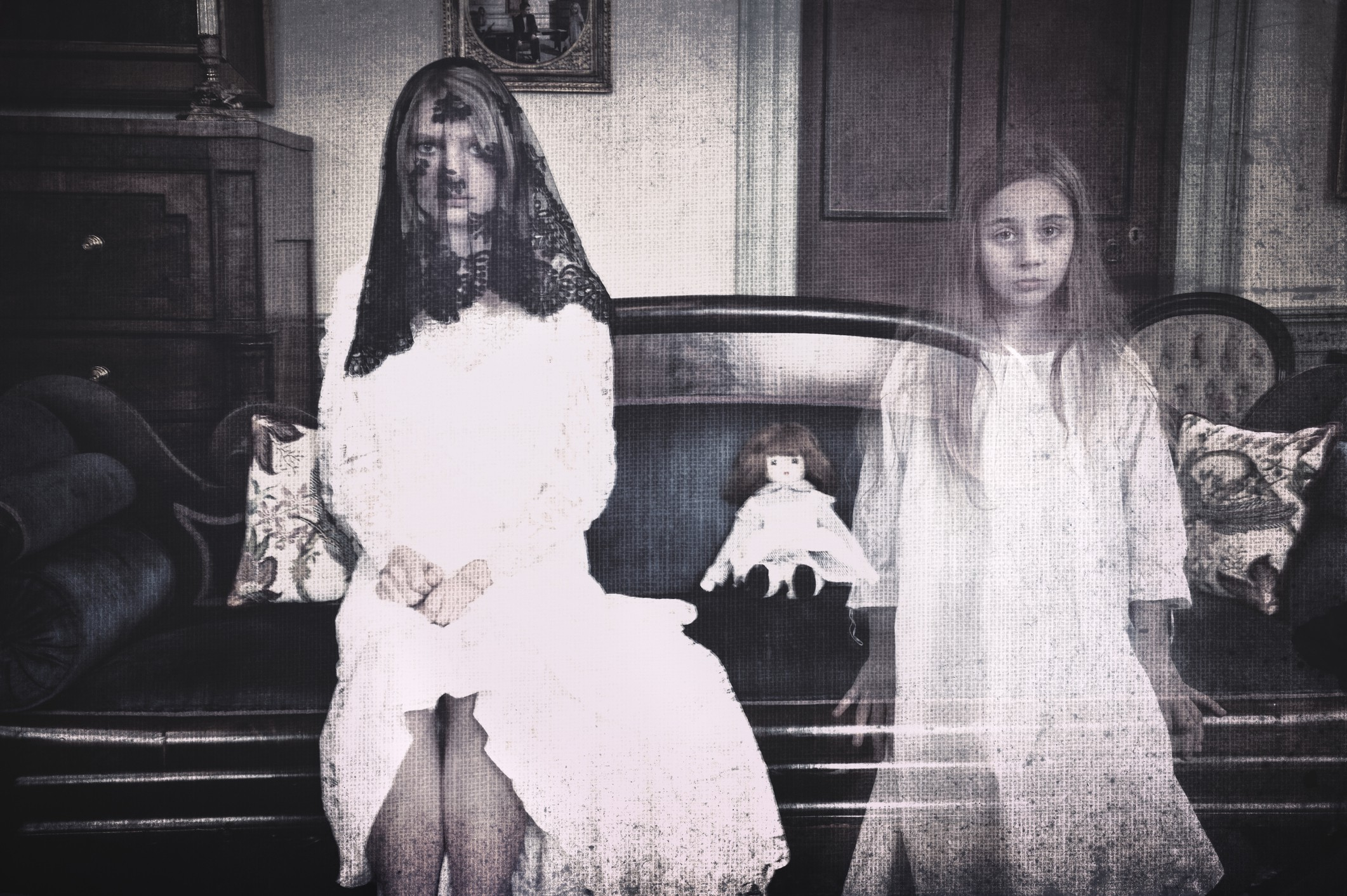 A black and white photo of two ghostly girls sitting on an antique couch with a creepy doll next to them.