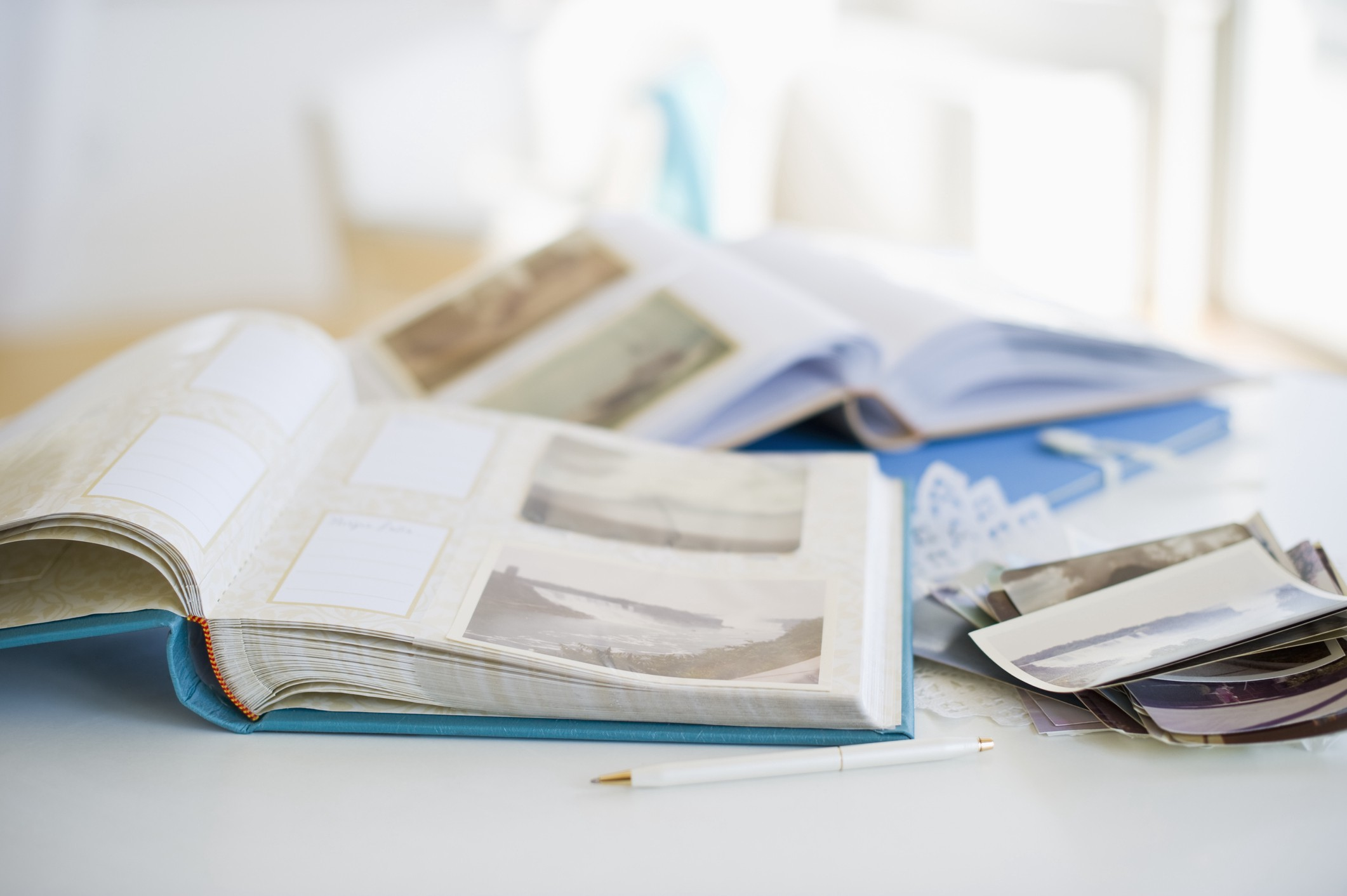 A photo of two photo scrapbooks on a table with some polaroids on the side.