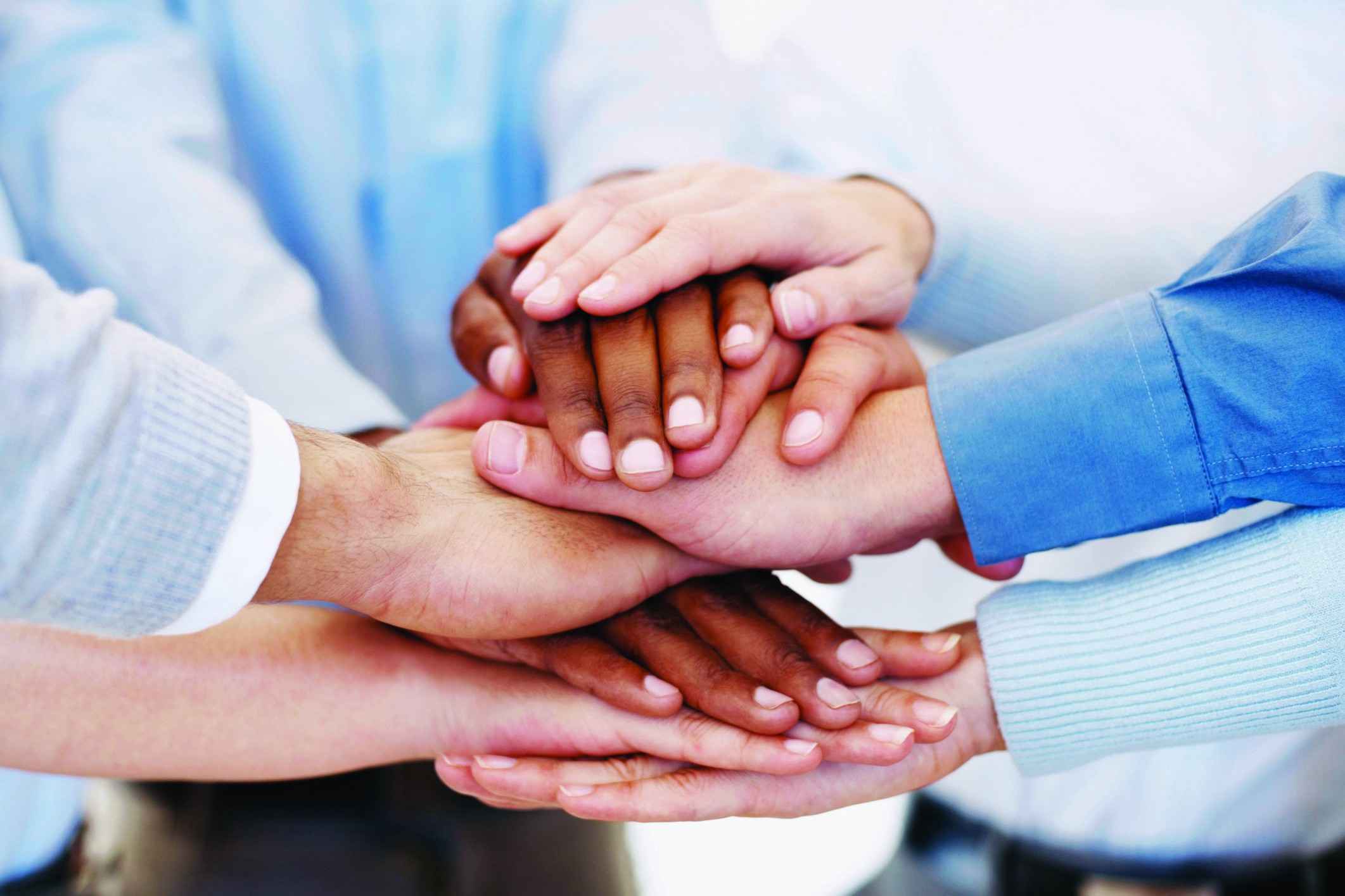 A series of different coloured human hands piled on top of each other, as to signify teamwork from a group of people