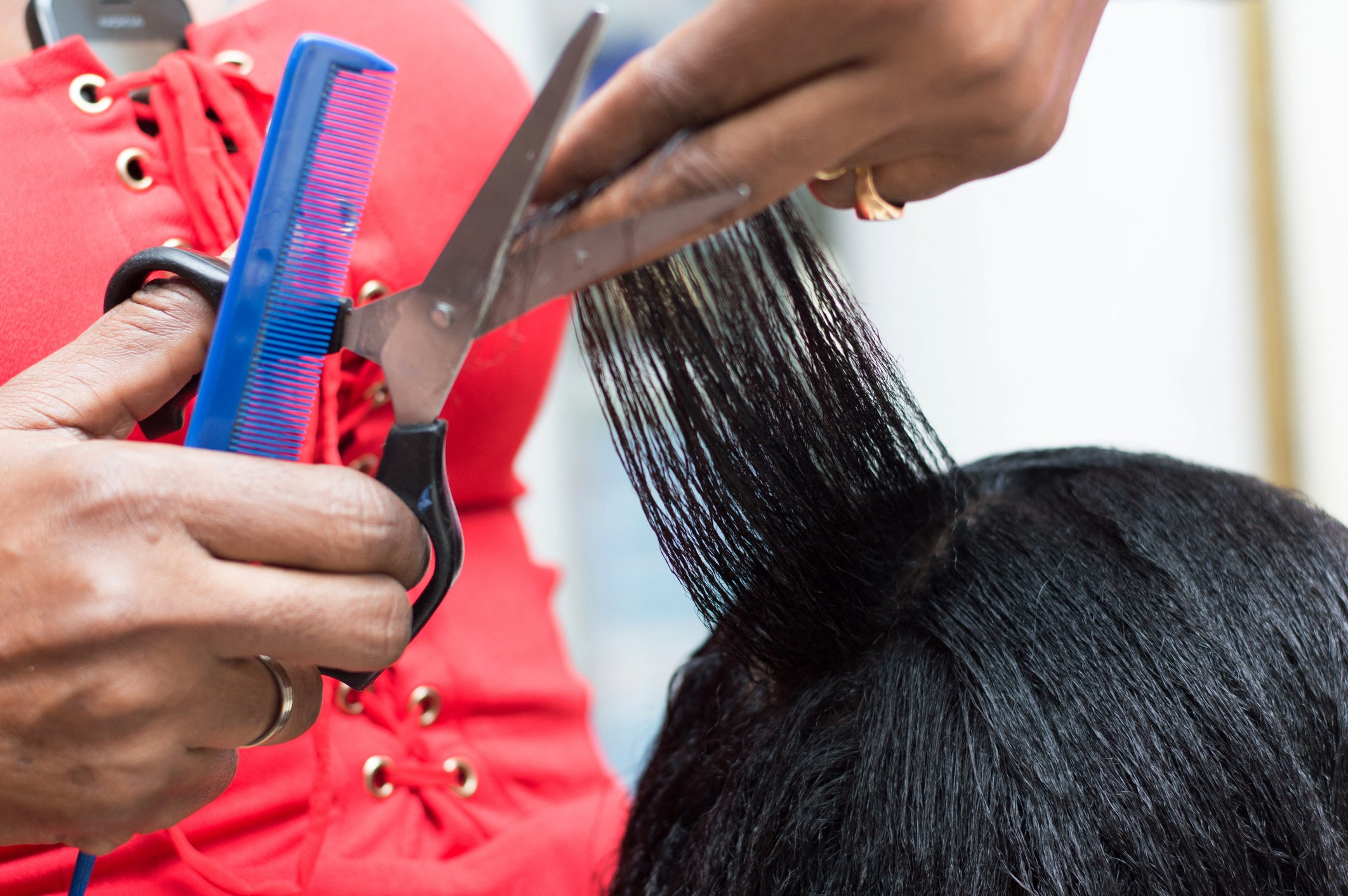 A closeup photo of a hair stylist cutting a client's hair.