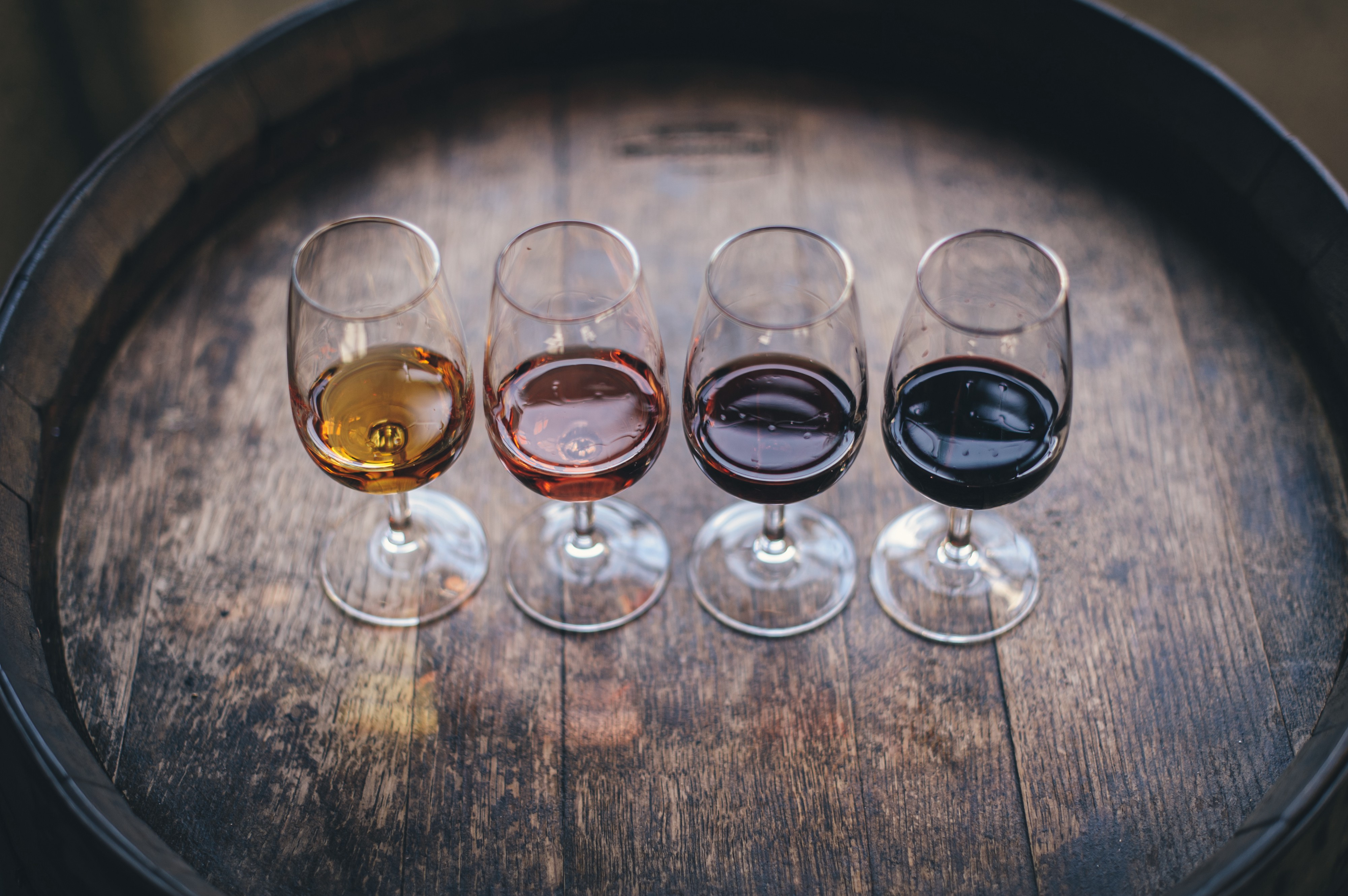 A wine tasting flight of colors from yellow to red sitting on top of an oak barrel.