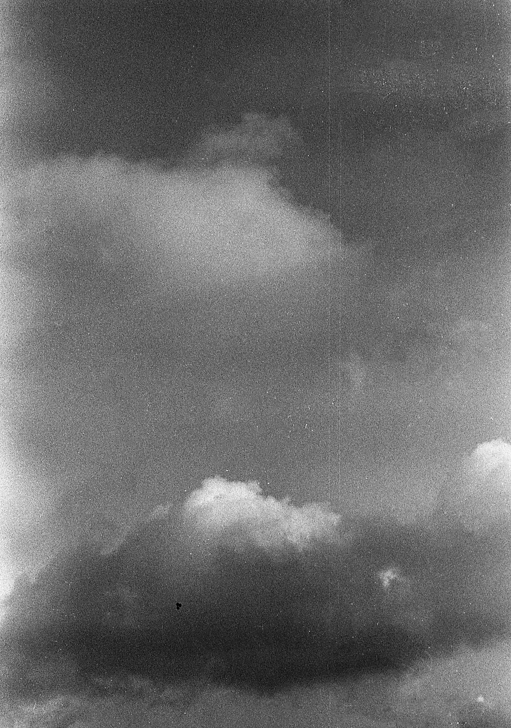 Greyscale photo of cloudy sky with old-photo noise filter.