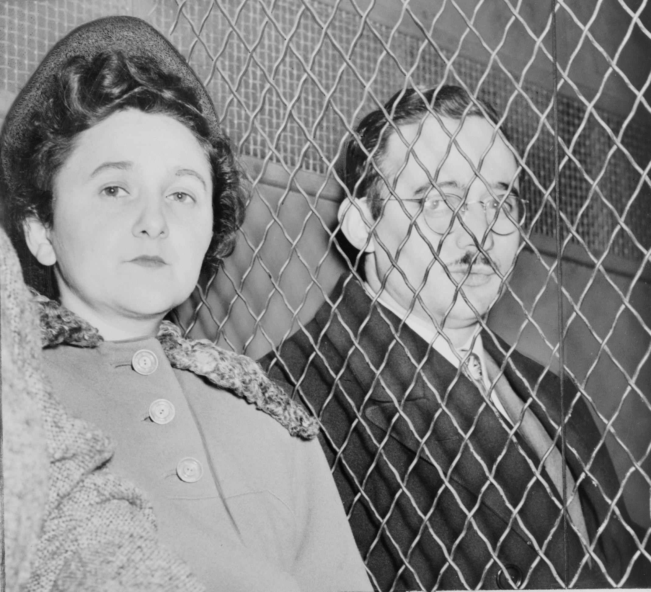 Ethel and Julius Rosenberg sitting on either side of a chain link fence