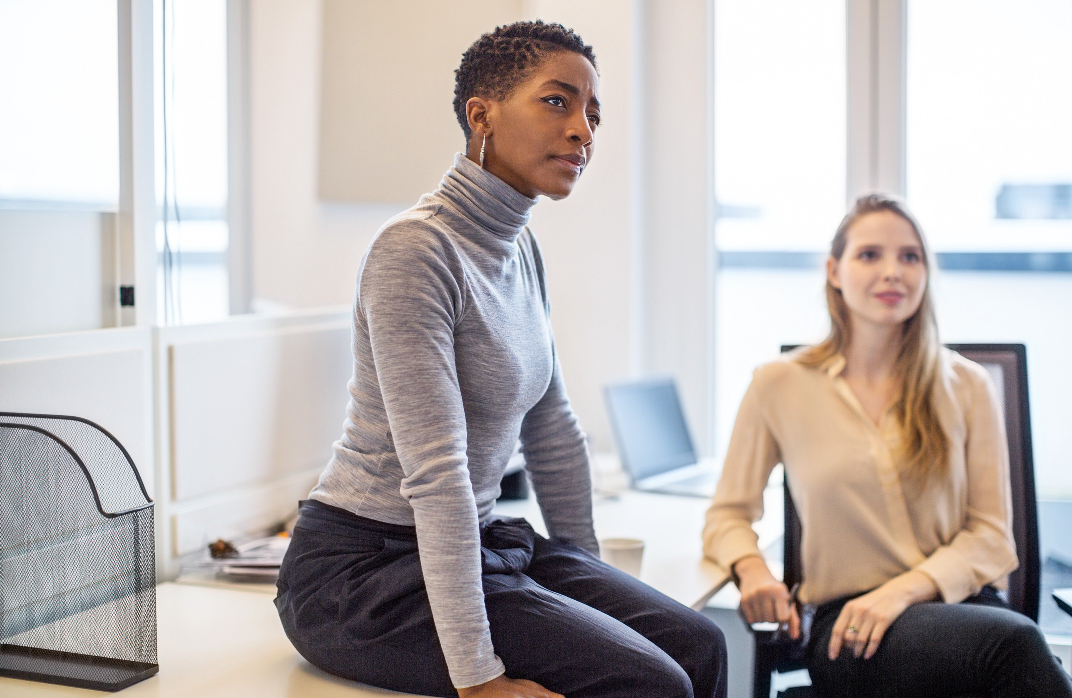A photo of a black woman in a work meeting with a perplexed expression.