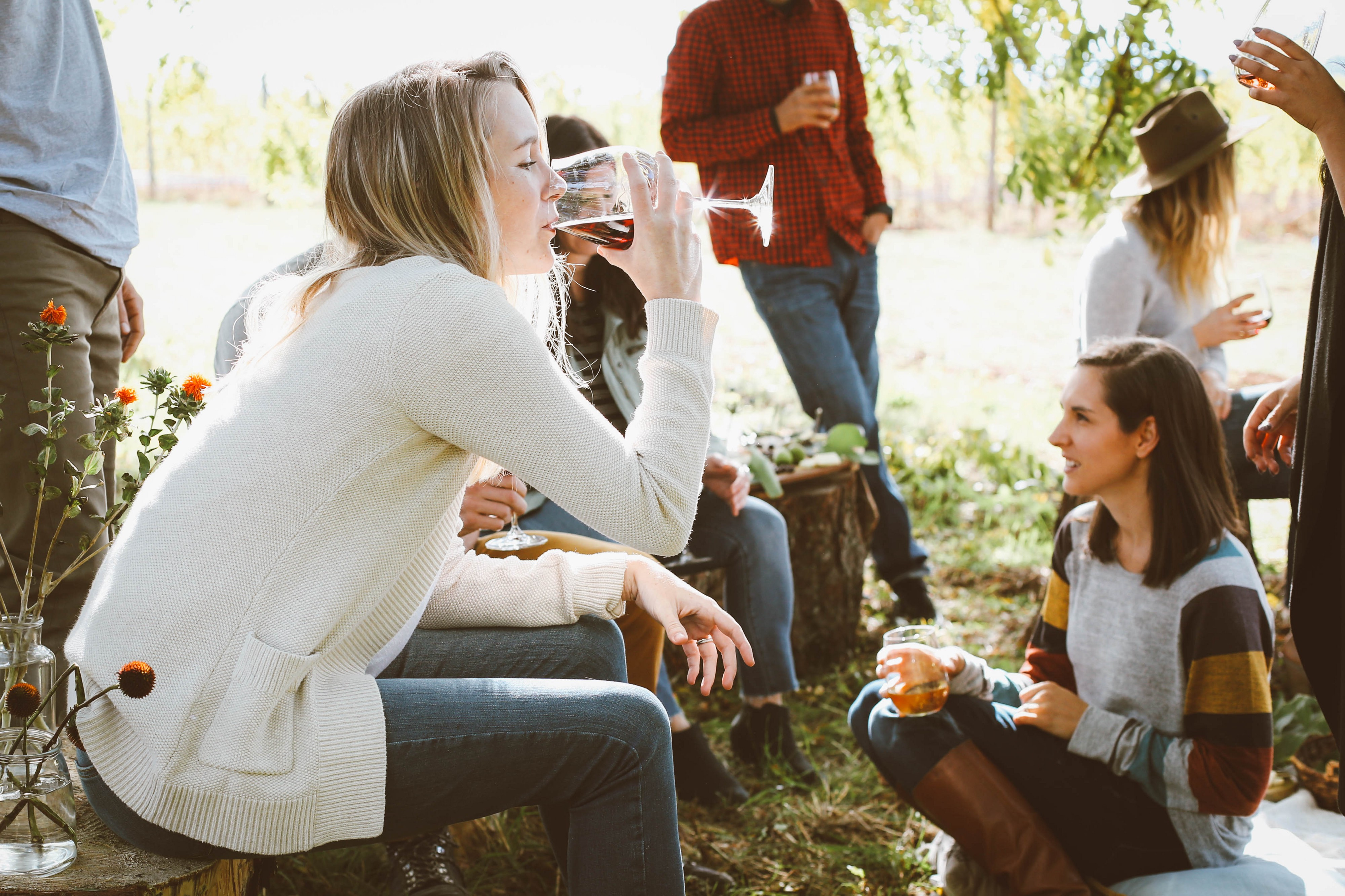 Friends drinking wine outside. A woman takes a sip of red wine.