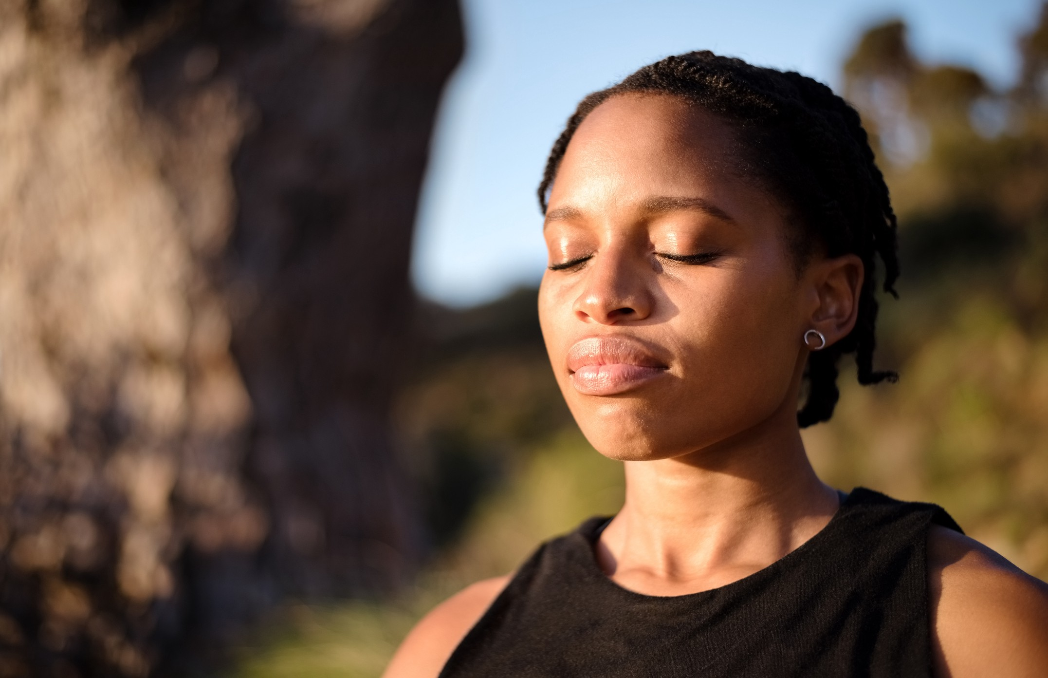 Close-up shot of healthy young woman meditating outdoors with her eyes closed.