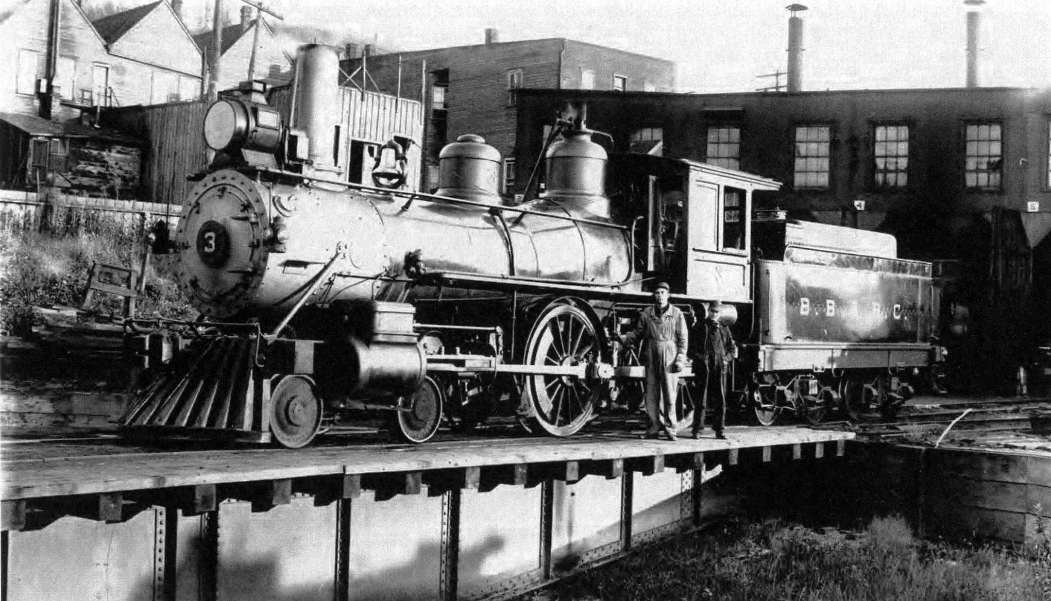 A old photo of a locomotive engine parked on the turntable near the roundhouse