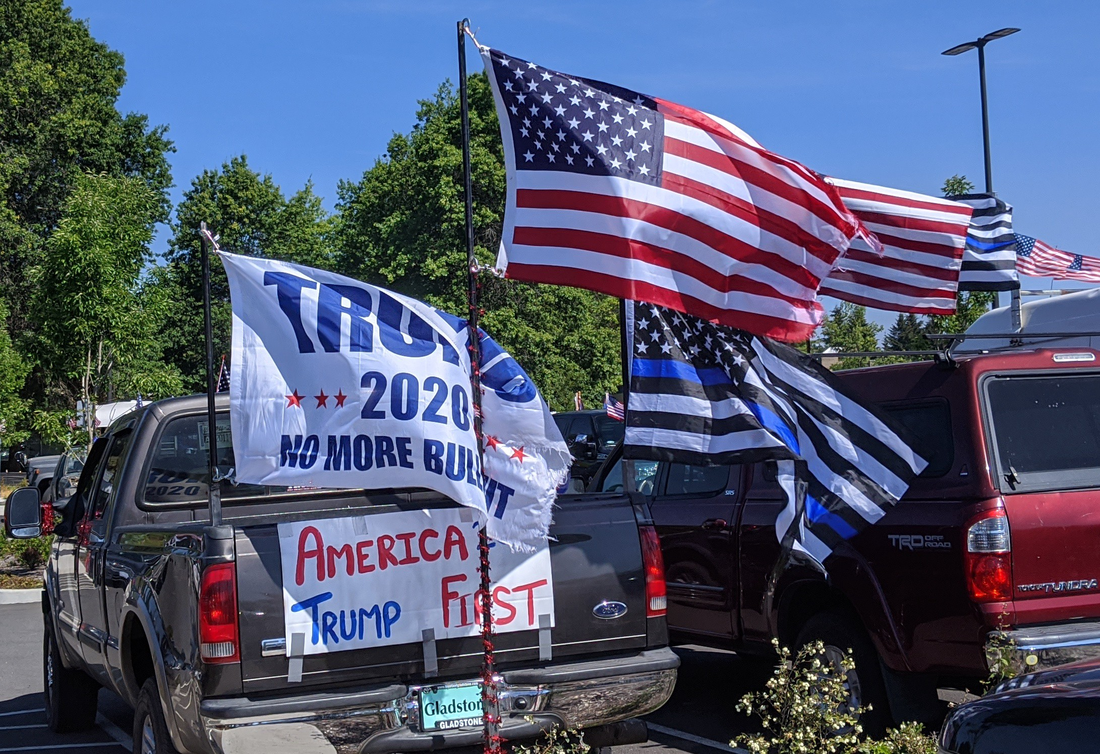 "A black pickup truck with the words ""AMERICA TRUMP FIRST"" on the back with a Trump 2020, Blue Lives Matter, and American flag"