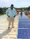 Andrew Ssentongo, founder of GRS Commodities, lends a hand during the installation of solar panels on Bukasa Island.