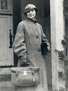 A woman in a trenchcoat and hat