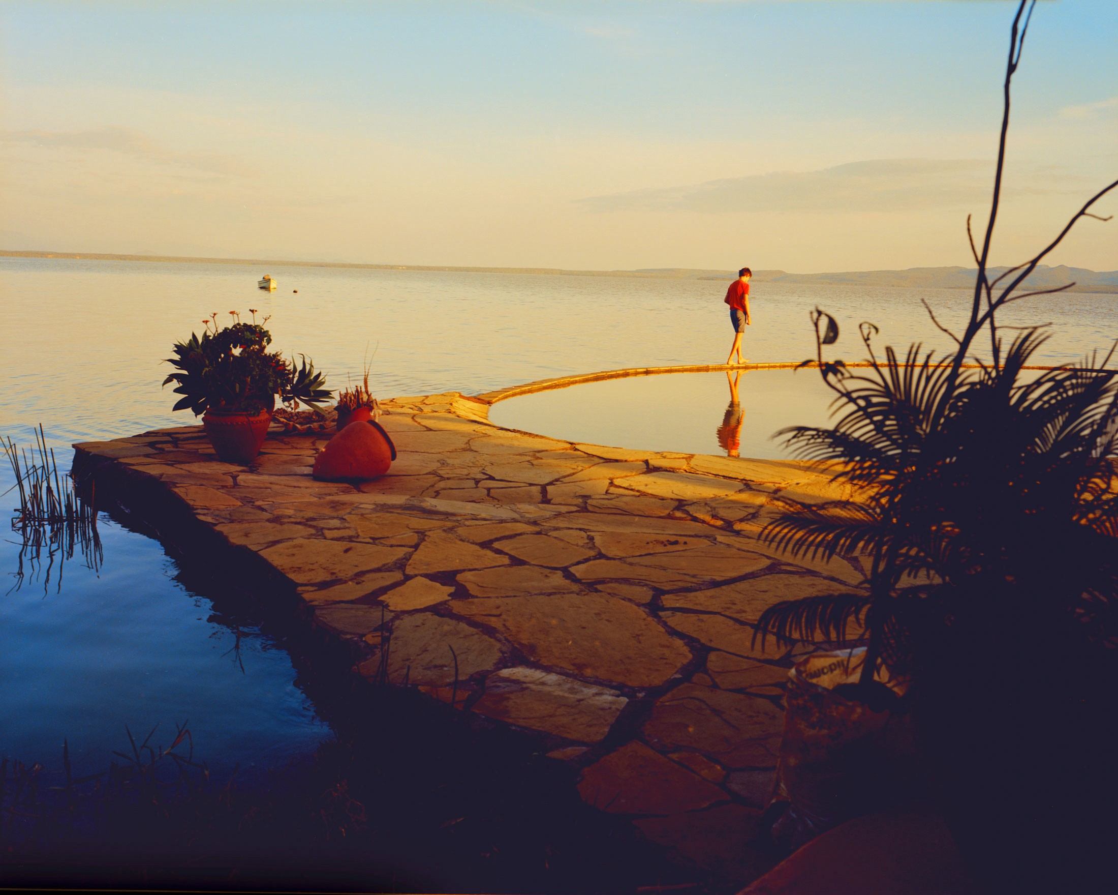 A person walks along the Kenyan island at sunset, with the lake in the background.