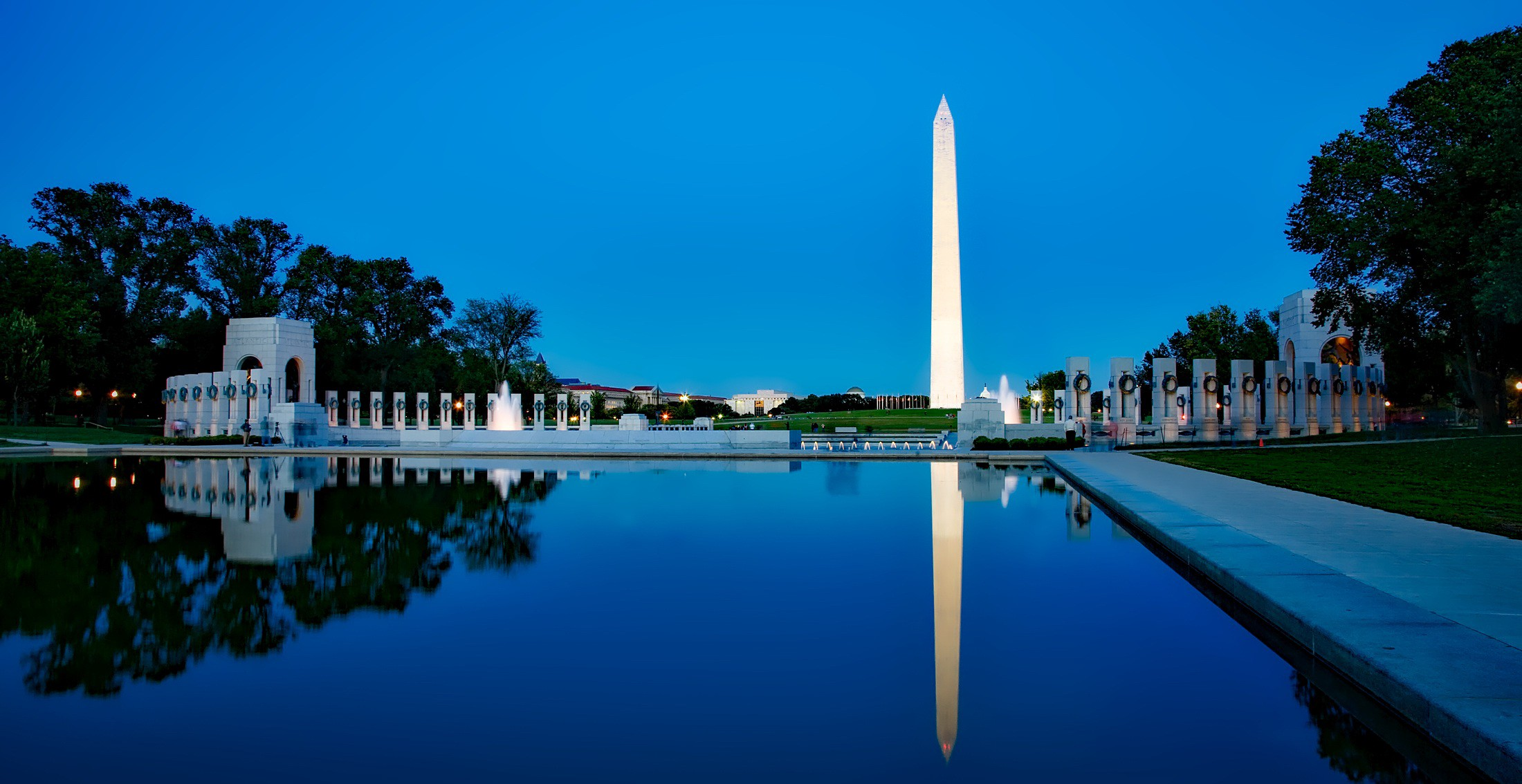 Wide shot of the Washington Monument and Lincoln Memorial Reflecting Pool at dusk with blue night sky and darker blue water