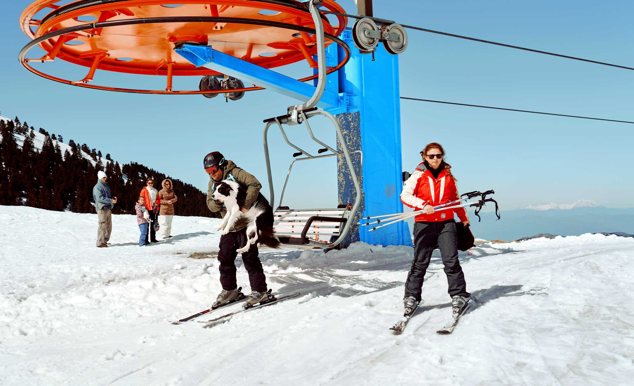 Skiers (one holding a dog) atop the ski lift at Mount Helmos in Greece.