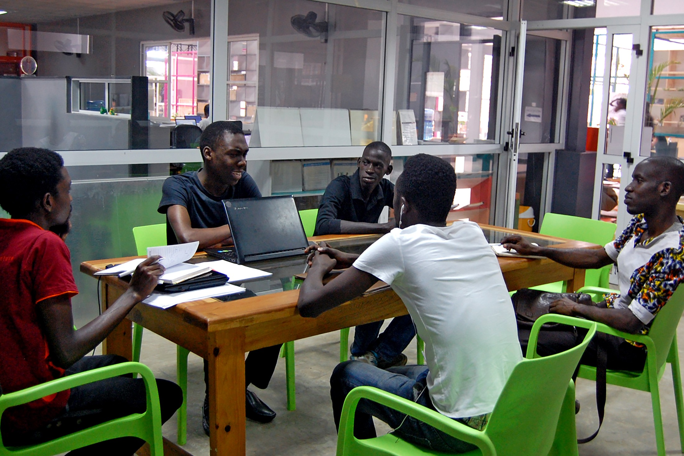 A group of young professionals in a meeting at a co-working space. Design Hub Kampala, Uganda.