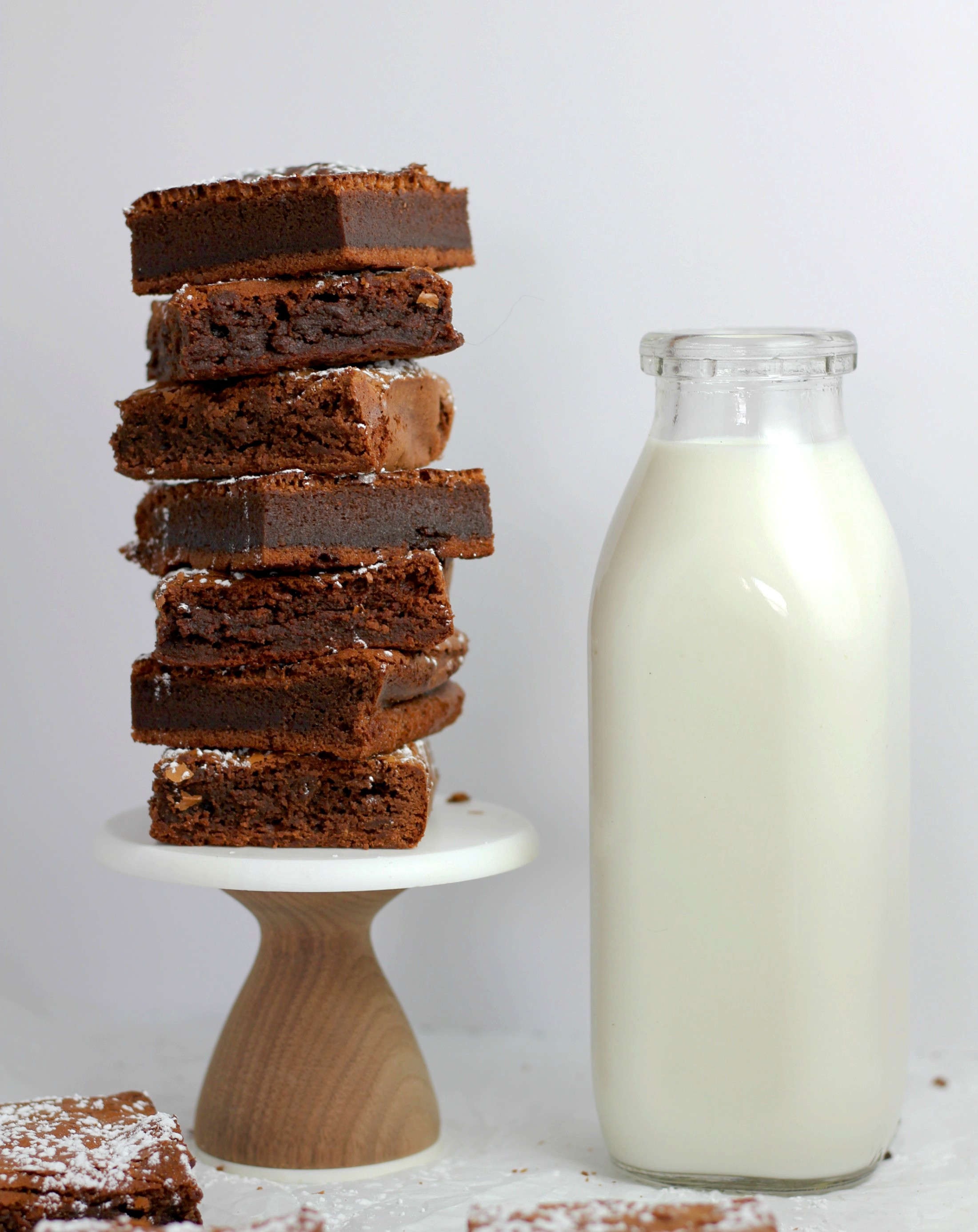 a jug of white milk next to a pile of chocolate brownies