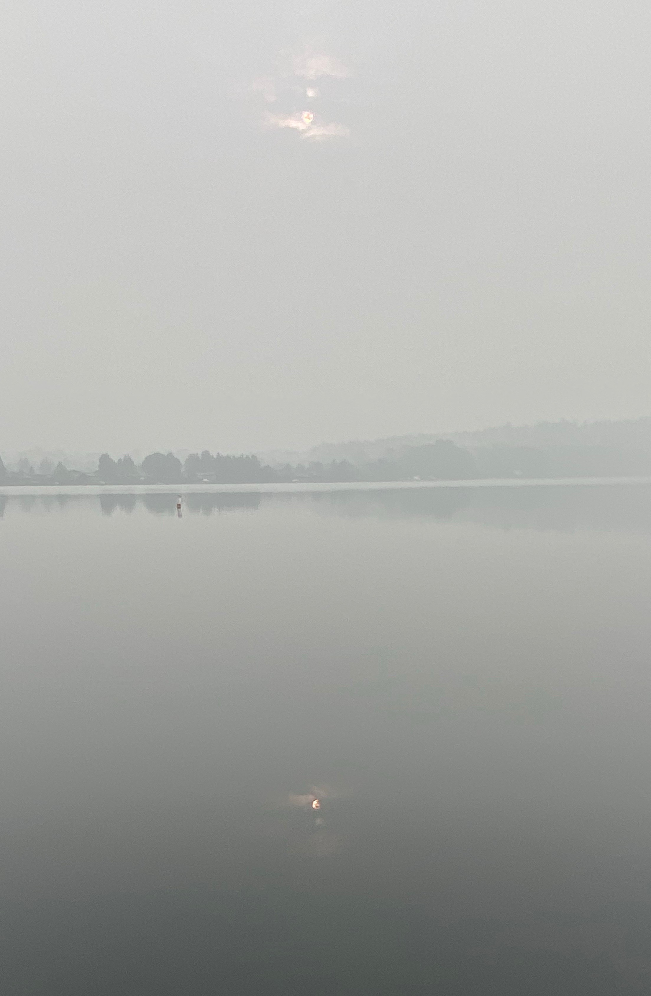 Lake with distant trees in hazy smokey sky.
