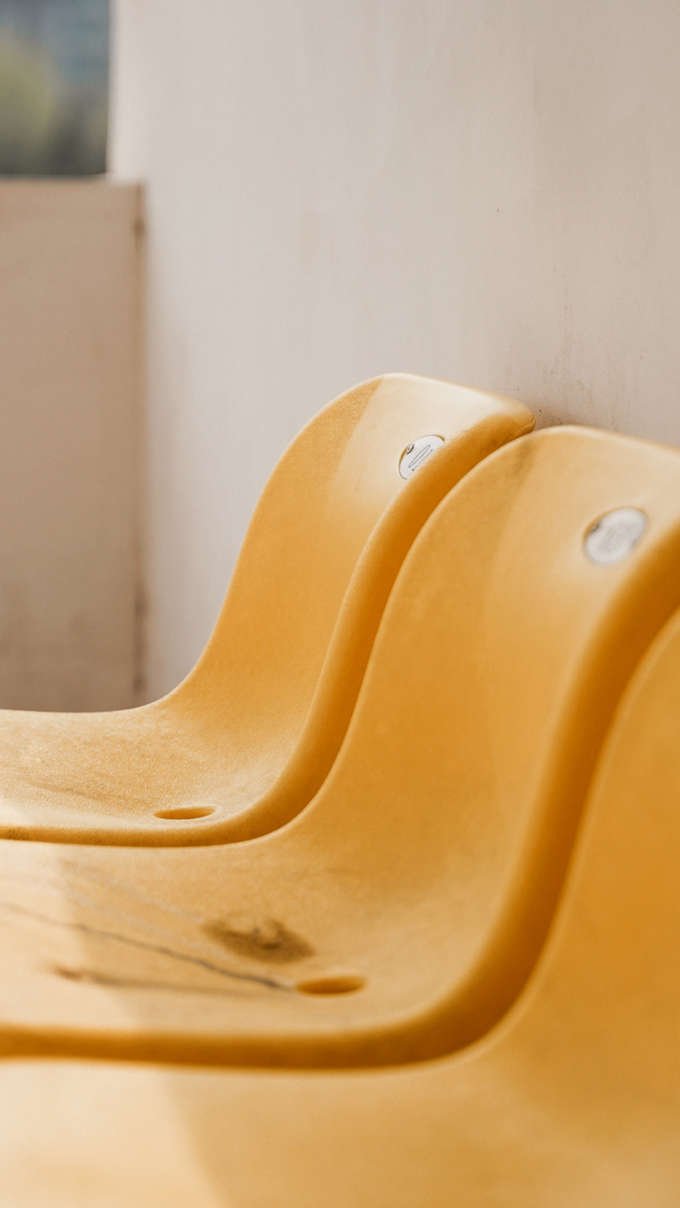 Hard yellow chair with a puddle of some liquid in it.