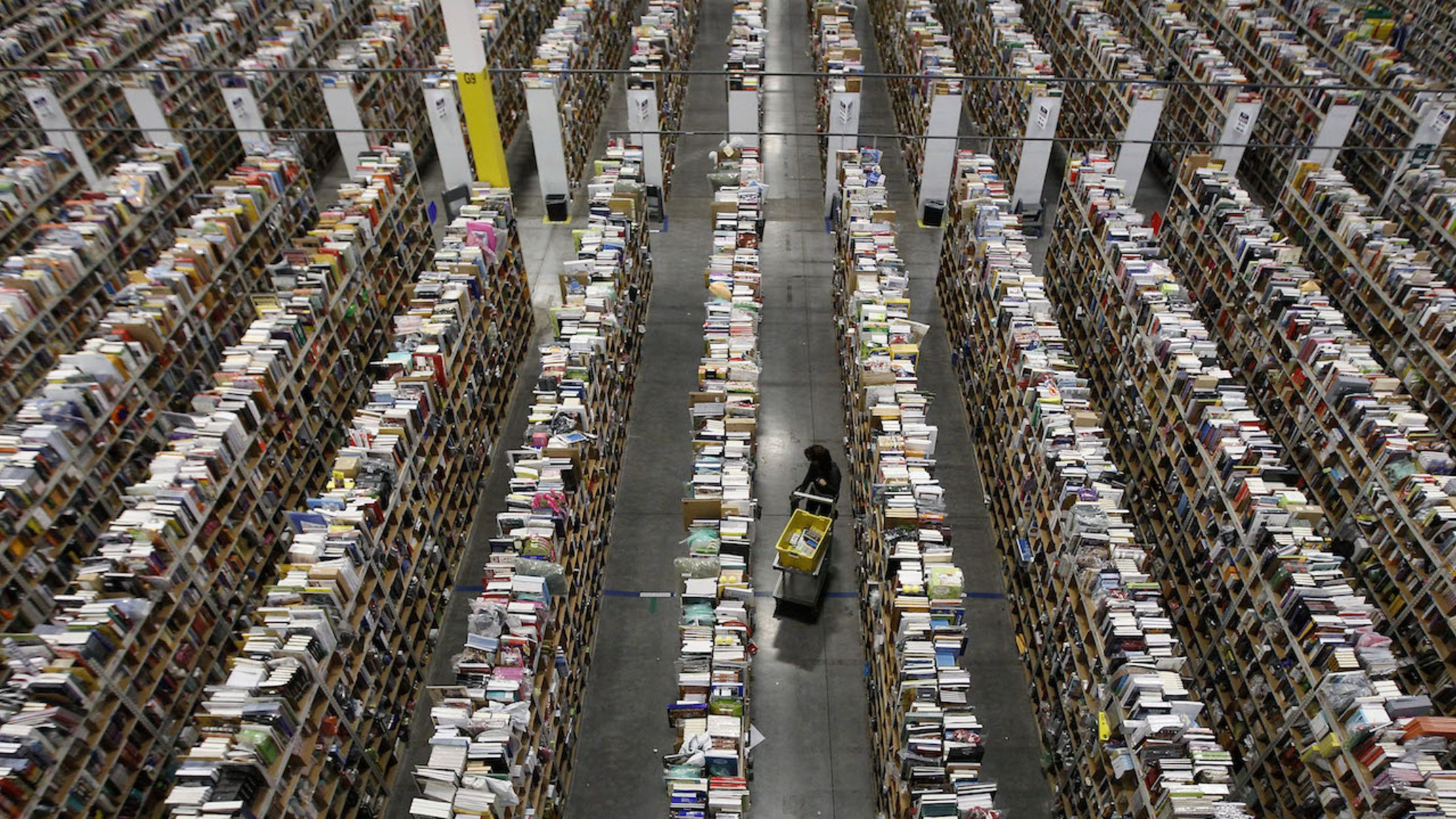 A lone worker pulls books from the endless shelves of the Amazon warehouse in Phoenix, AZ