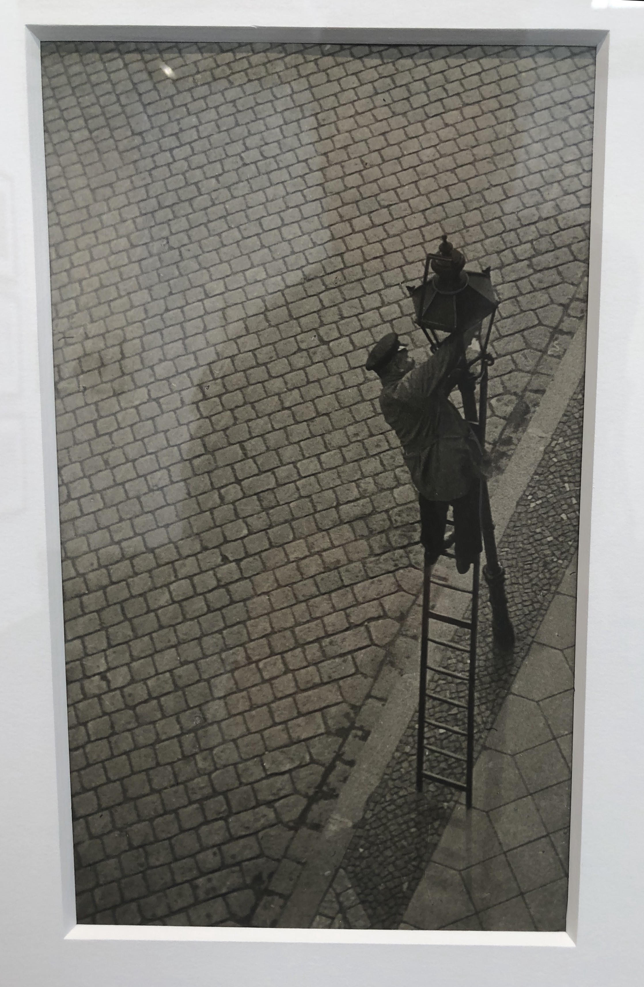 Black and white photograph of a man on a ladder working on a streetlamp.