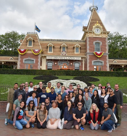 A group of people smiling, standing in front of a large mickey mouse face at Disneyland.
