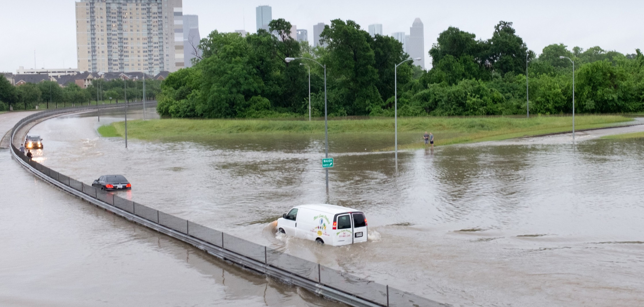 A van driving along a road in Houston, Texas is submerged in water during a flood event.