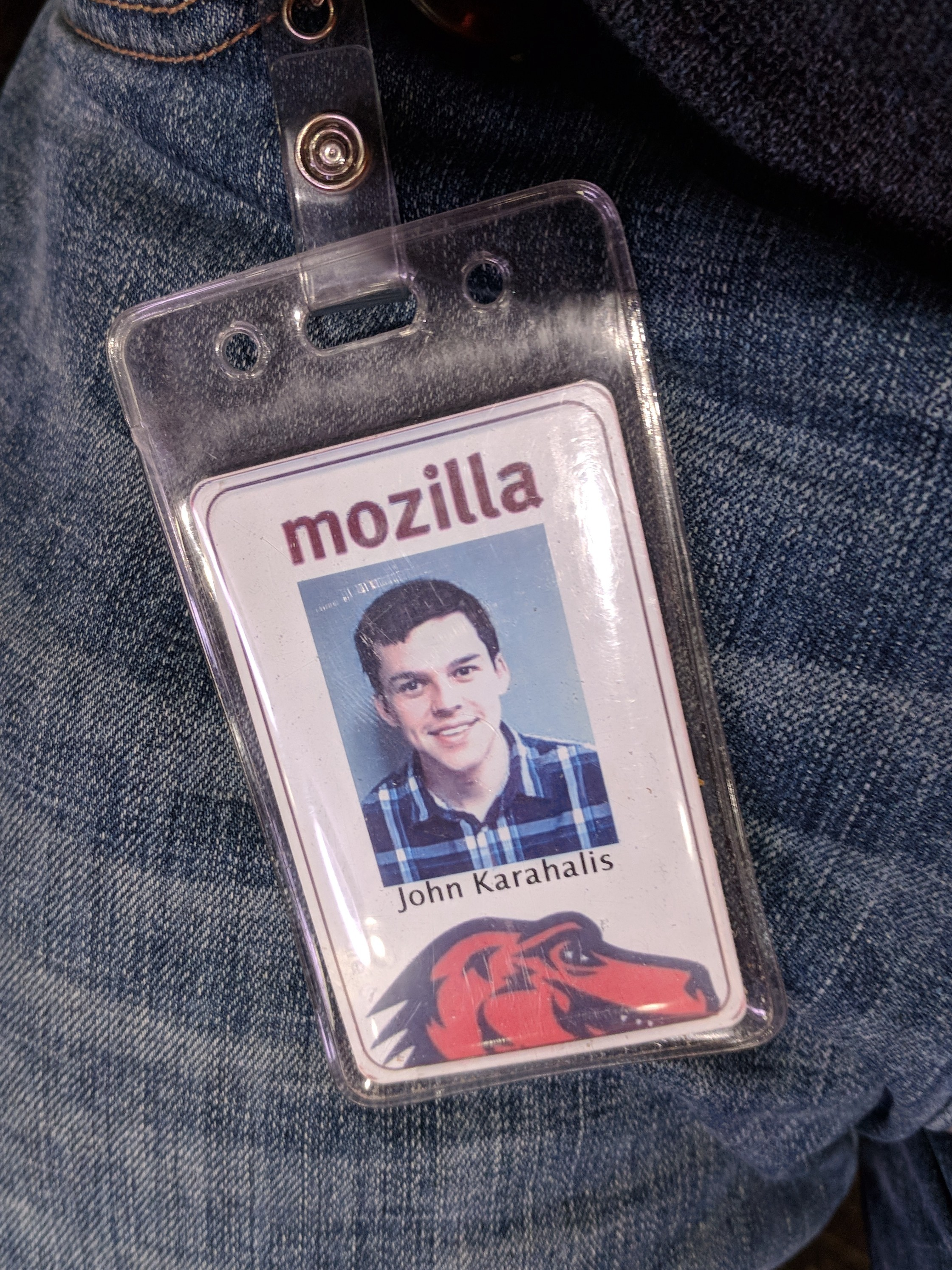 The employee badge for John Karahalis resting against his jeans