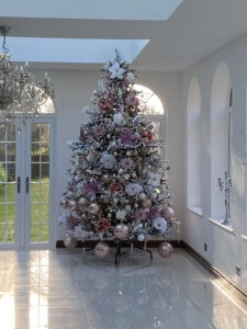 Christmas tree adorned with feathers, flowers and baubles in an orangery