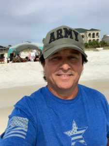 Skip Drish wearing an army hat on the beach
