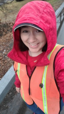 The author walking down the street in the rain. Wearing a red rain coat with the hood up and an orange reflective vest.
