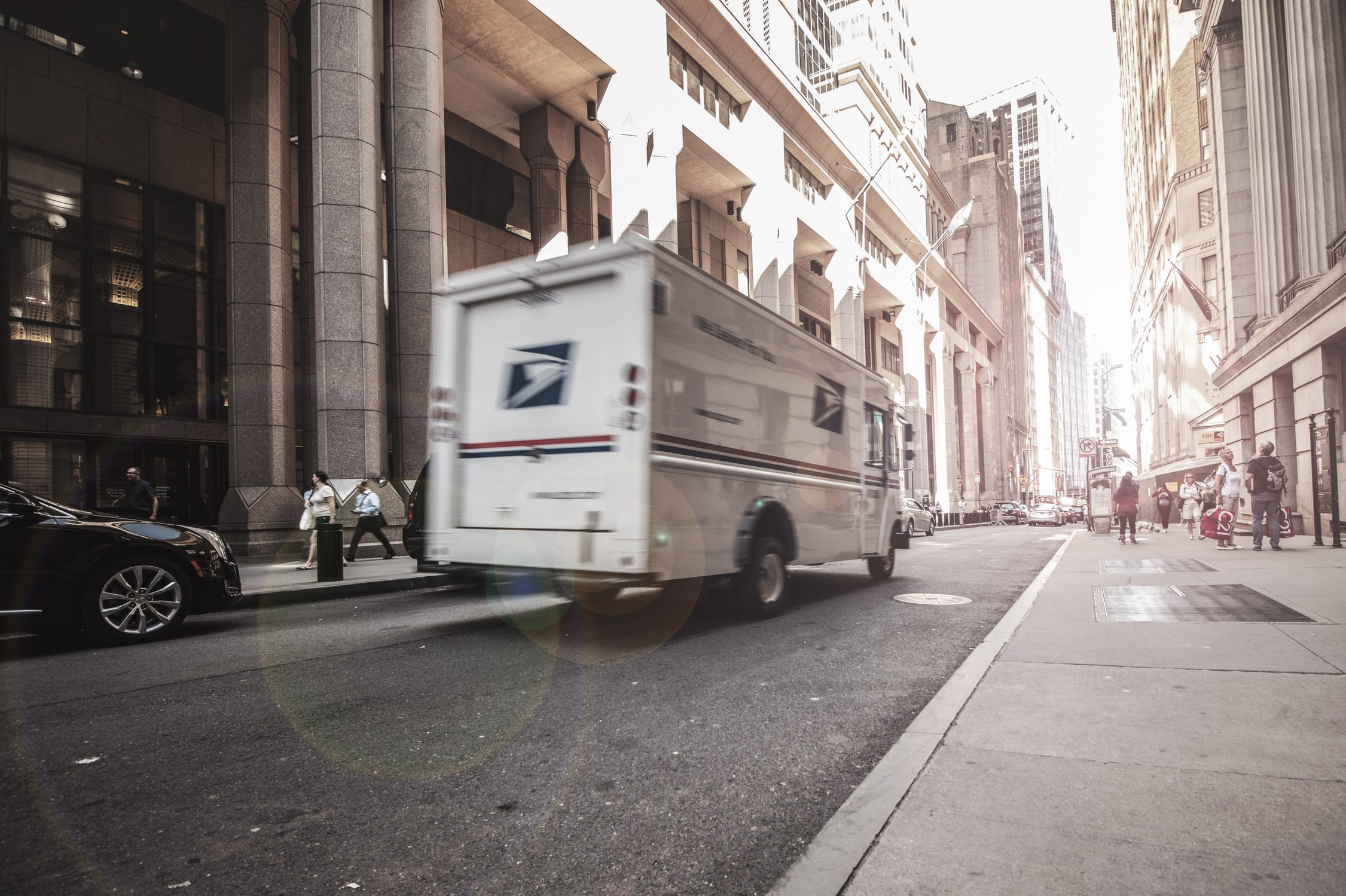USPS van making a delivery in a city