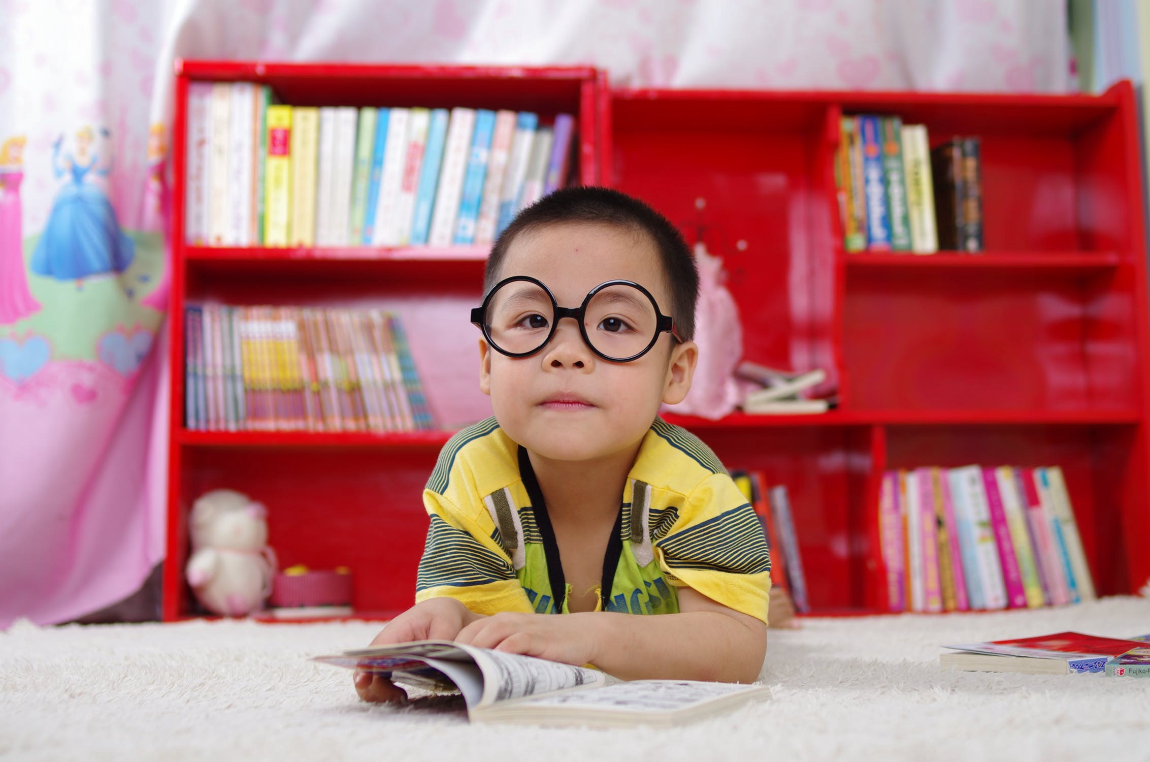 child with glasses and book