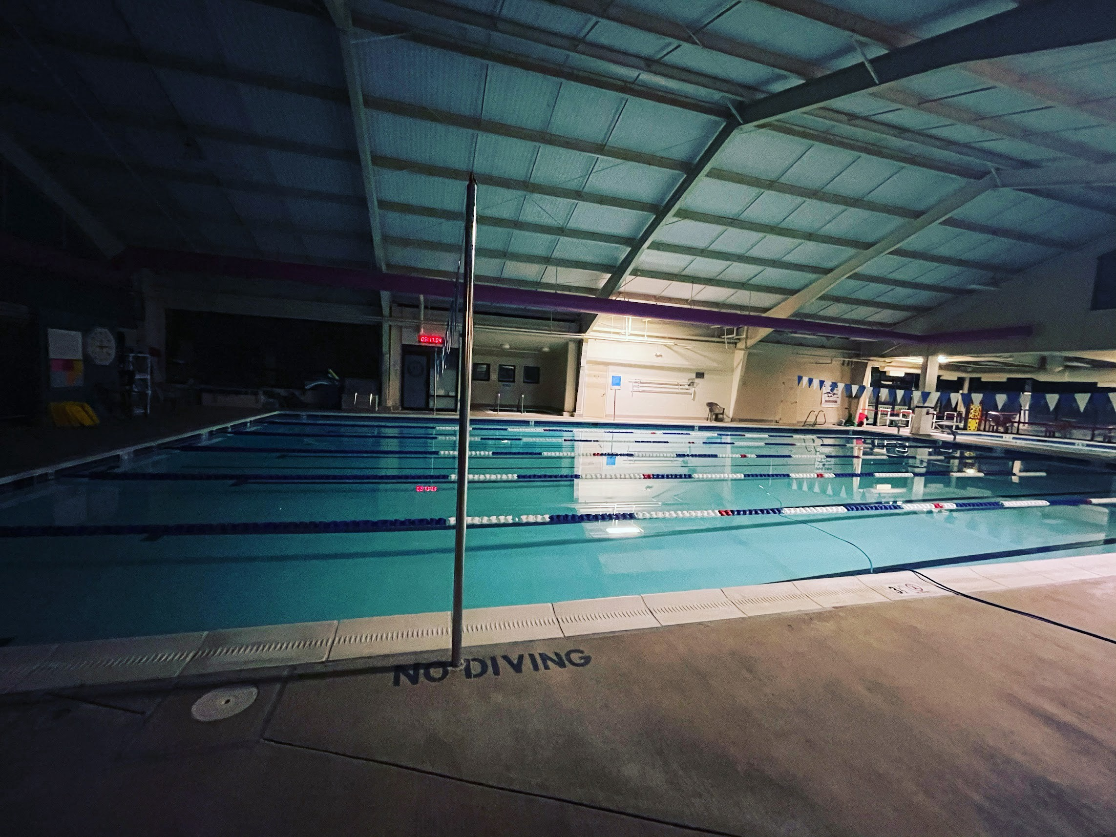 A swimming pool in the dark, with only low lighting. The swimming pool is divided into lanes for lap swimming.