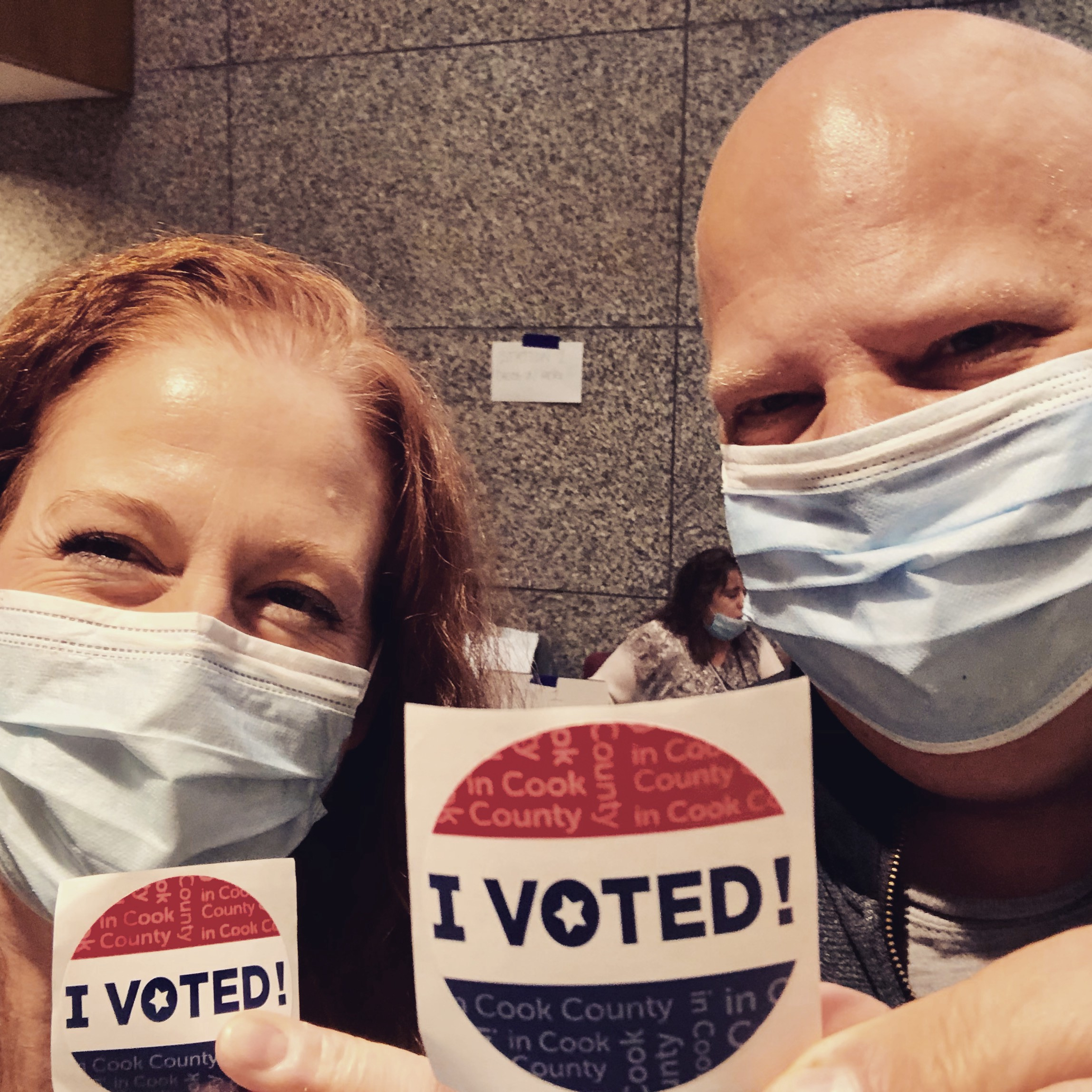 "Photo of the author and her husband, wearing masks, and holding up ""I Voted"" stickers."
