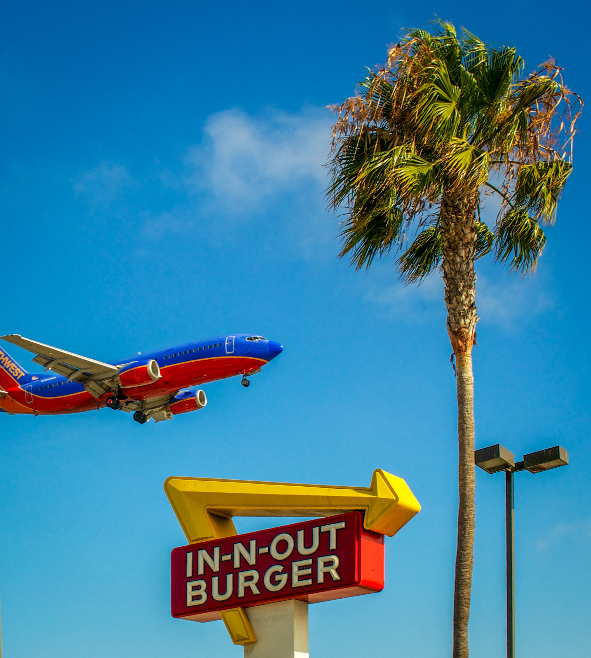 Airliner flying over In-N-Out sign.