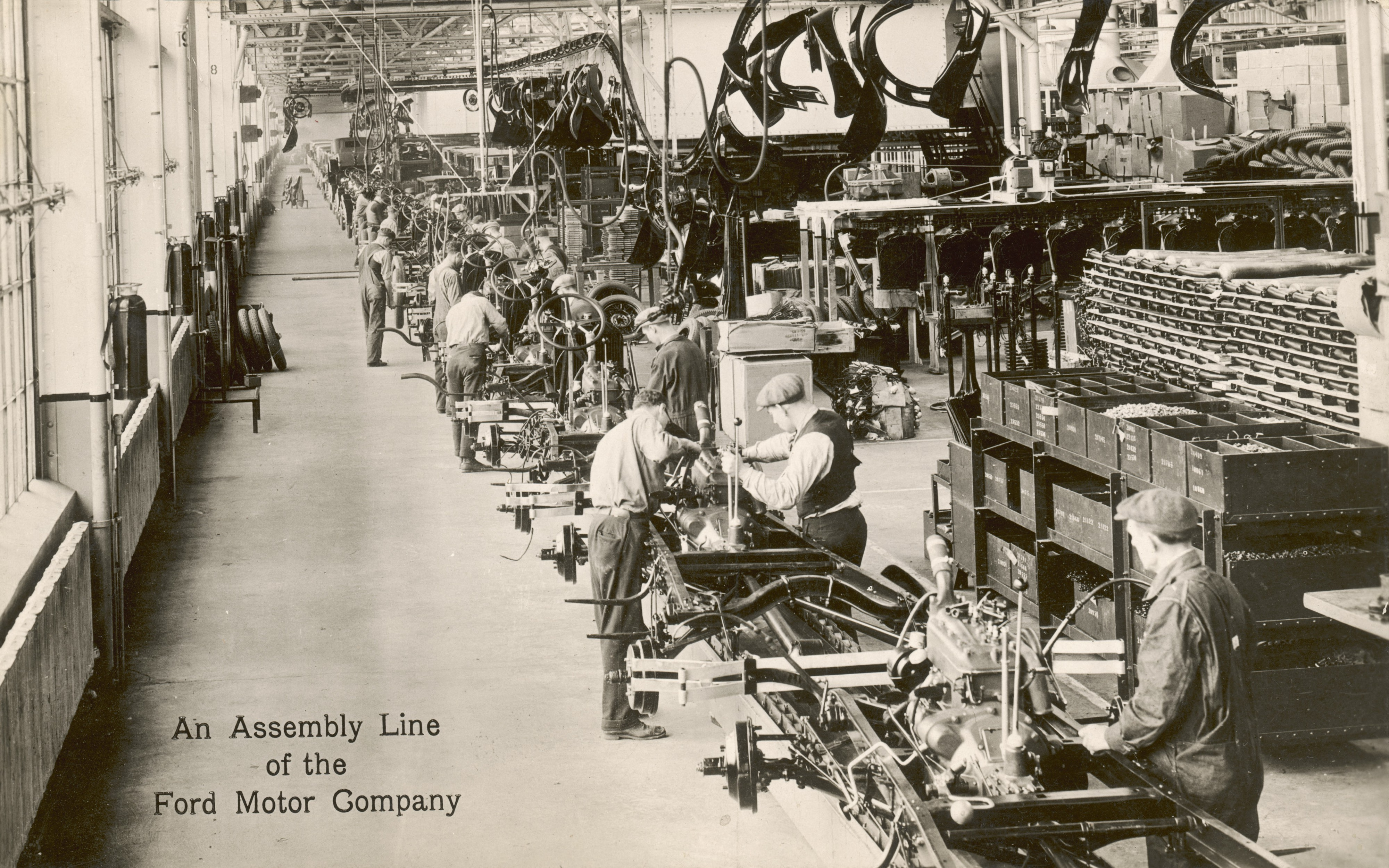 Sepia photograph of a Ford assembly line from the early Twentieth Century.