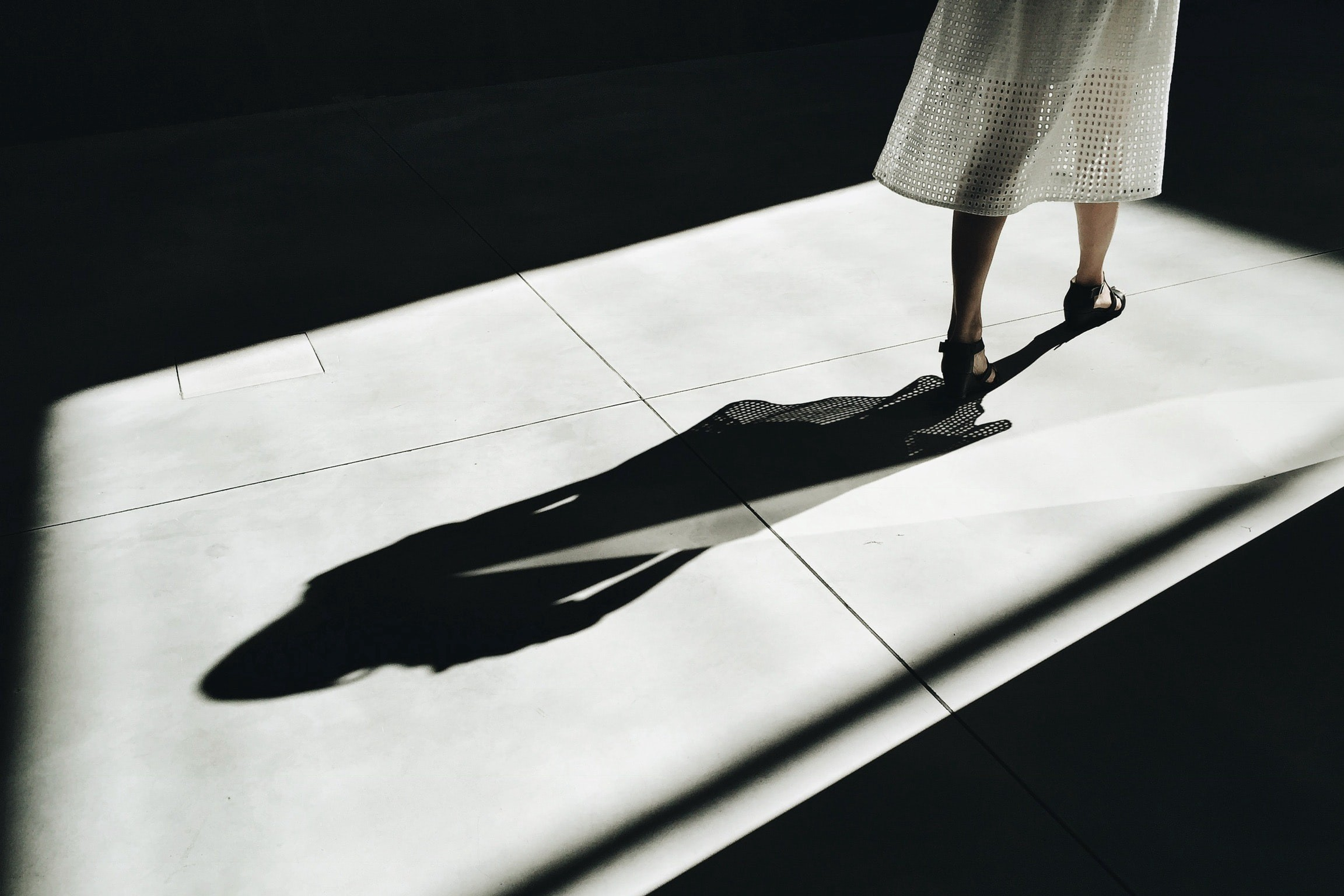 Photo of a woman walking away, her shadow at the center.