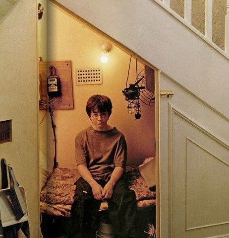Photo of Daniel Radcliffe as Harry Potter sitting on a bed in a cupboard under the stairs.