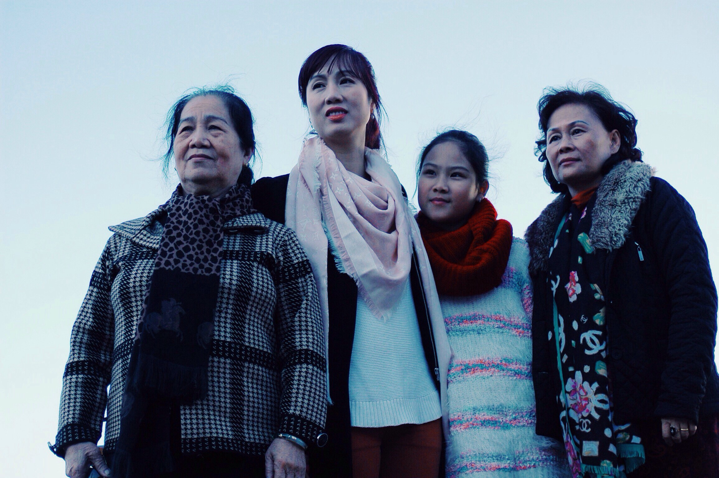 Four generations of Asian women stand in a group and look forward together.